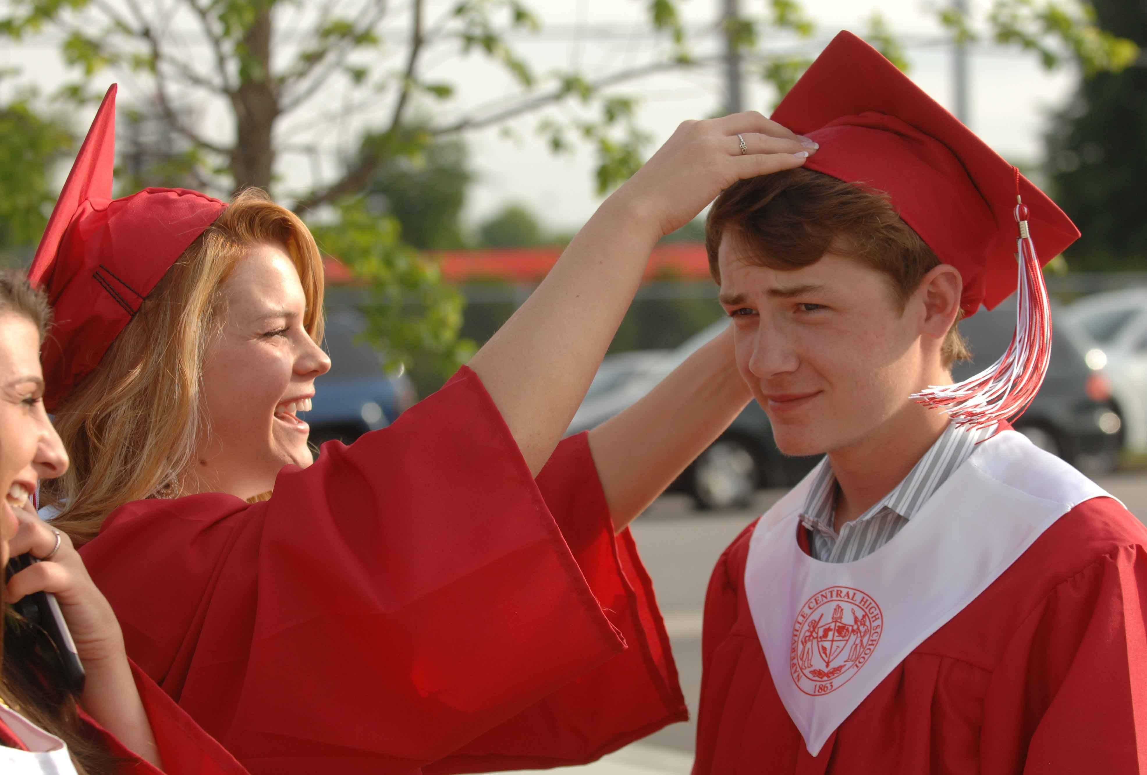 Kelly O'Halloran,left, helps Jack Tobin with his cap just before the Naperville Central High School Commencement Wednesday.