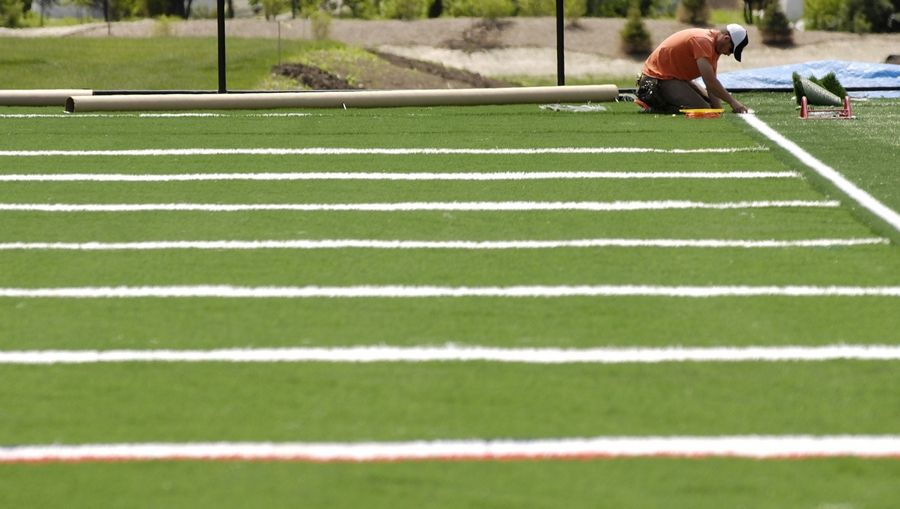 Turf seams are stitched in place as the Nike Sports Complex in Naperville nears completion.