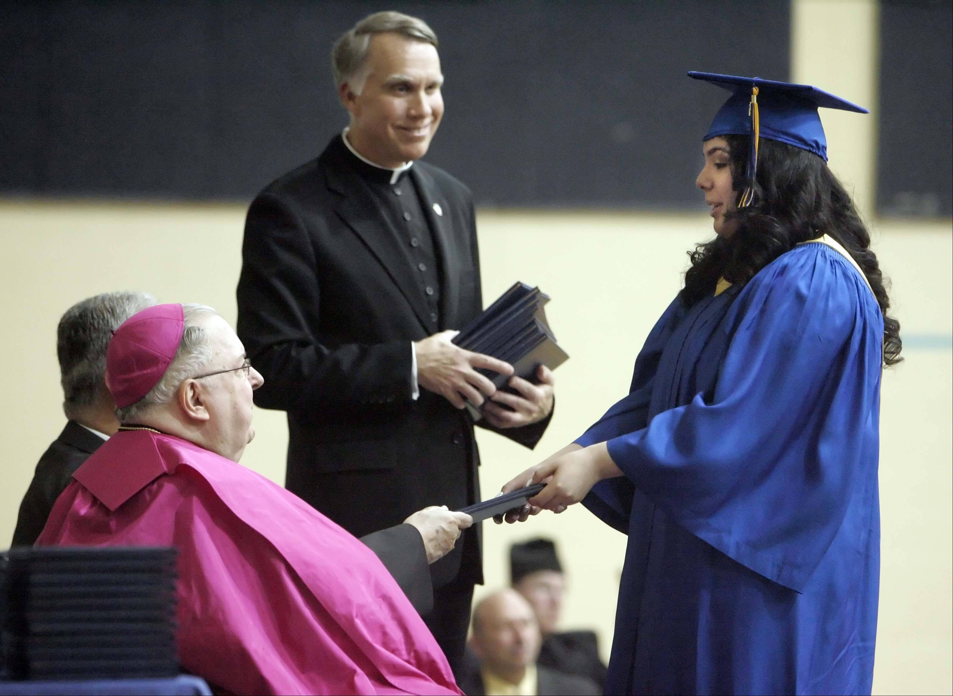 Ariana Aquiniga, receives her diploma from Most Rev. Thomas G. Doran, Bishop of Rockford, seated, during Aurora Central Catholic High School graduation Thursday, May 26, 2011 in Aurora.
