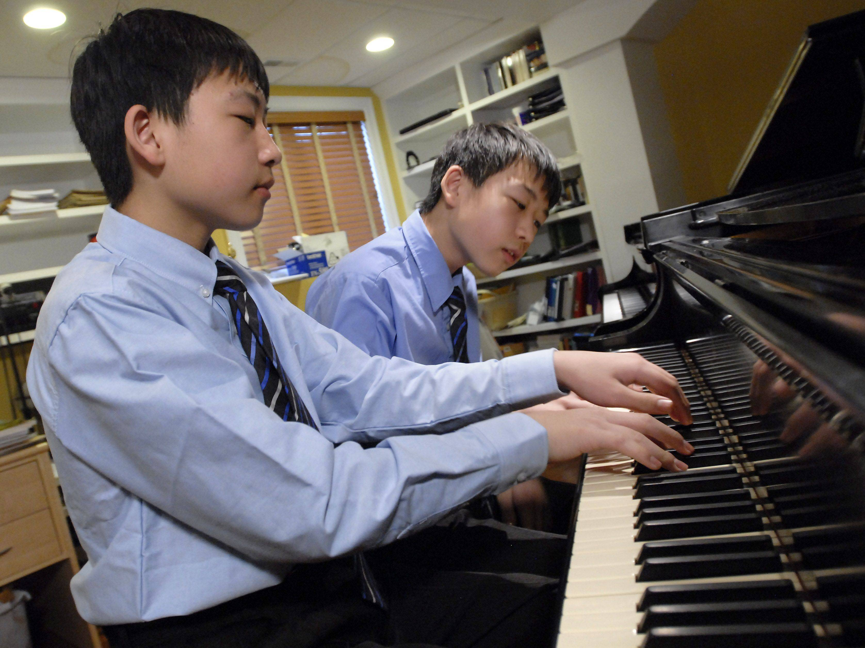 Twins Kyle, left, and Ryan Jannak-Huang of Palatine are 13-year-old classical pianists. They are playing a piece written for four hands.