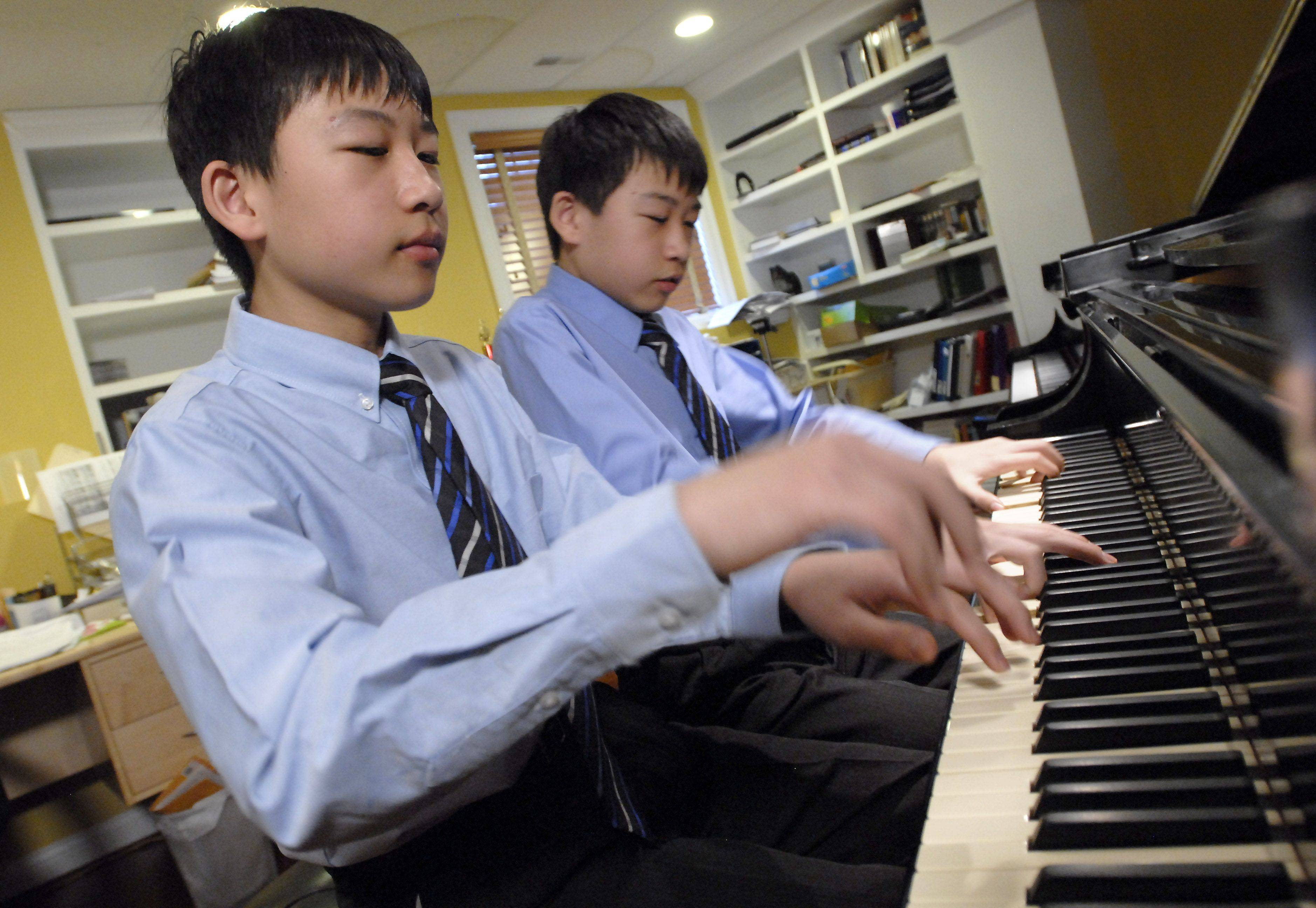 Twins Kyle, left, and Ryan Jannak-Huang of Palatine are 13-year-old classical pianists.