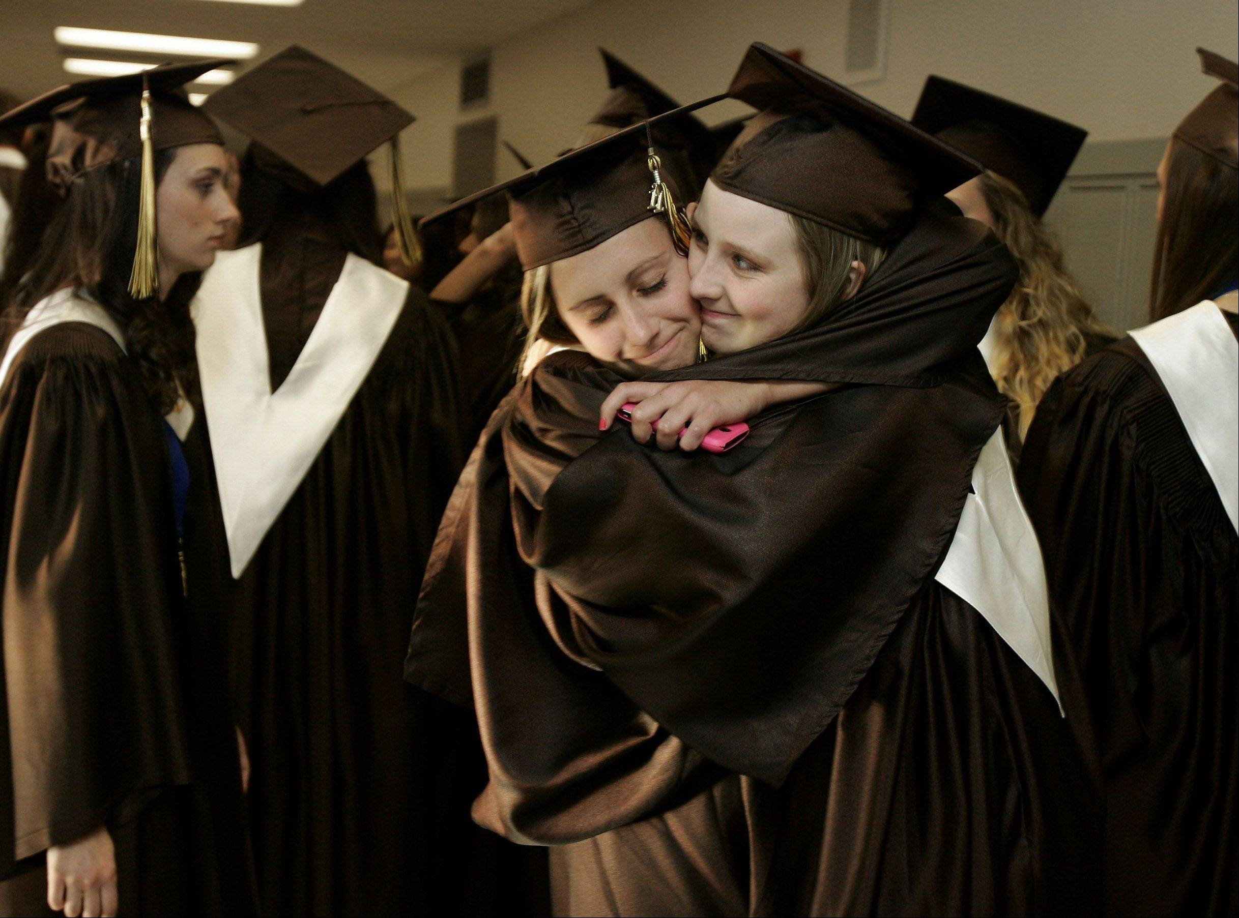 Allison Michel, left, and Lauren Bowles hug in the hall before the start of the commencement ceremony at Carmel Catholic High School Thursday evening. The graduating Class of 2011 consisted of 308 seniors.