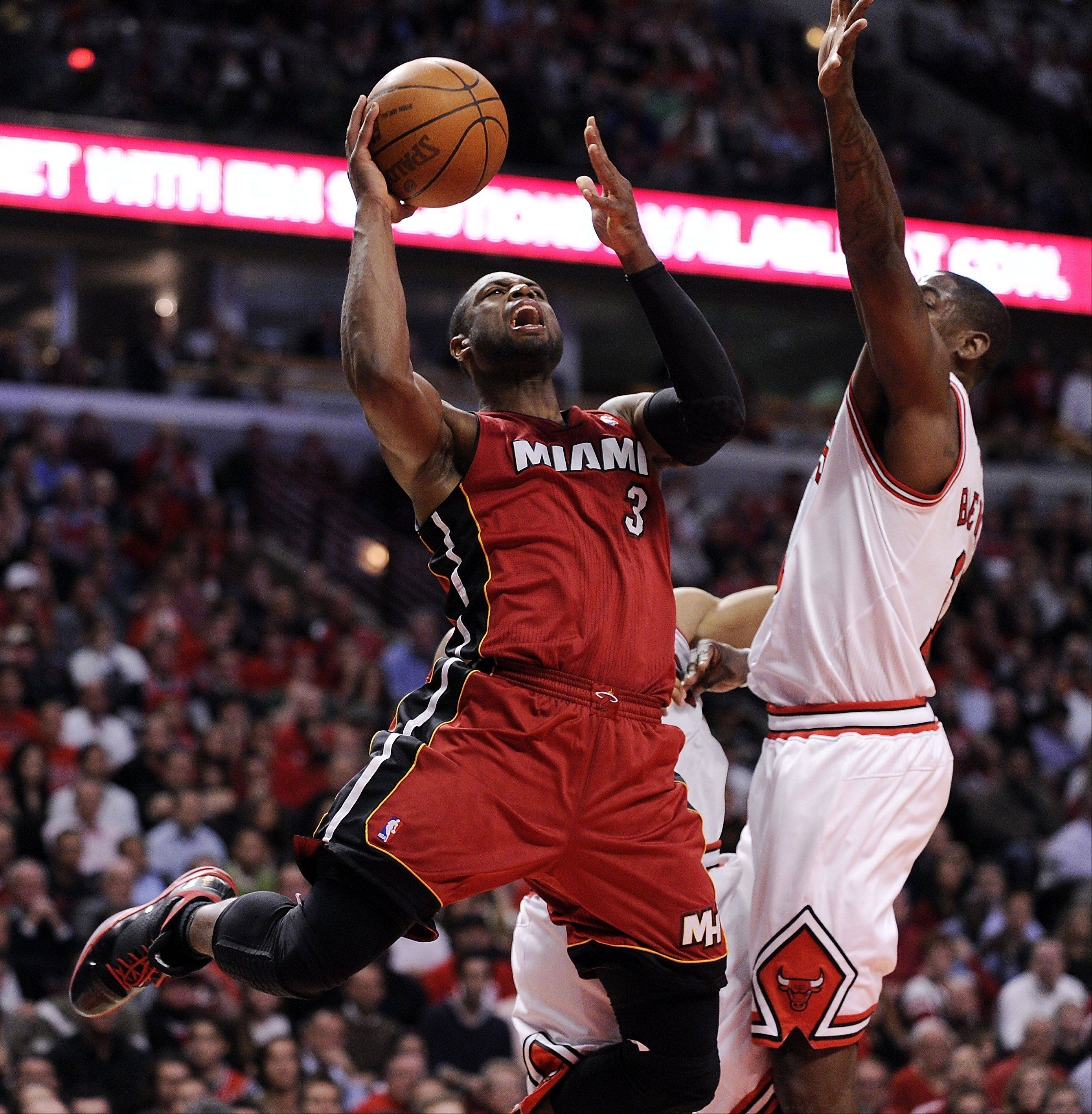 The Heat's Dwyane Wade goes up against Bulls' Ronnie Brewer in the fourth quarter.