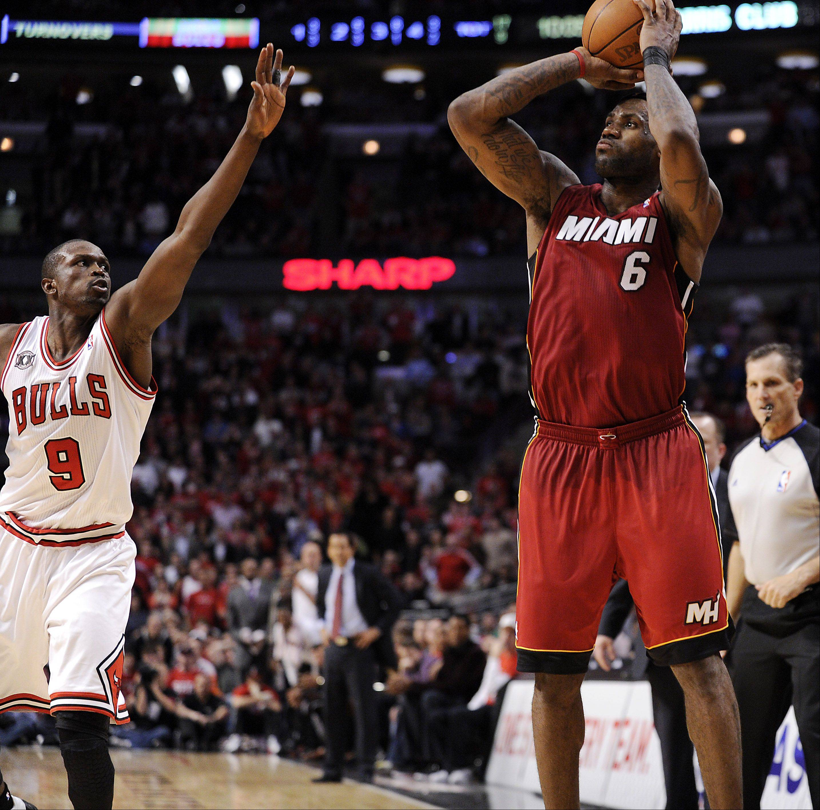 The Heat's LeBron James shoots over the Bulls' Luol Deng late in the fourth quarter.