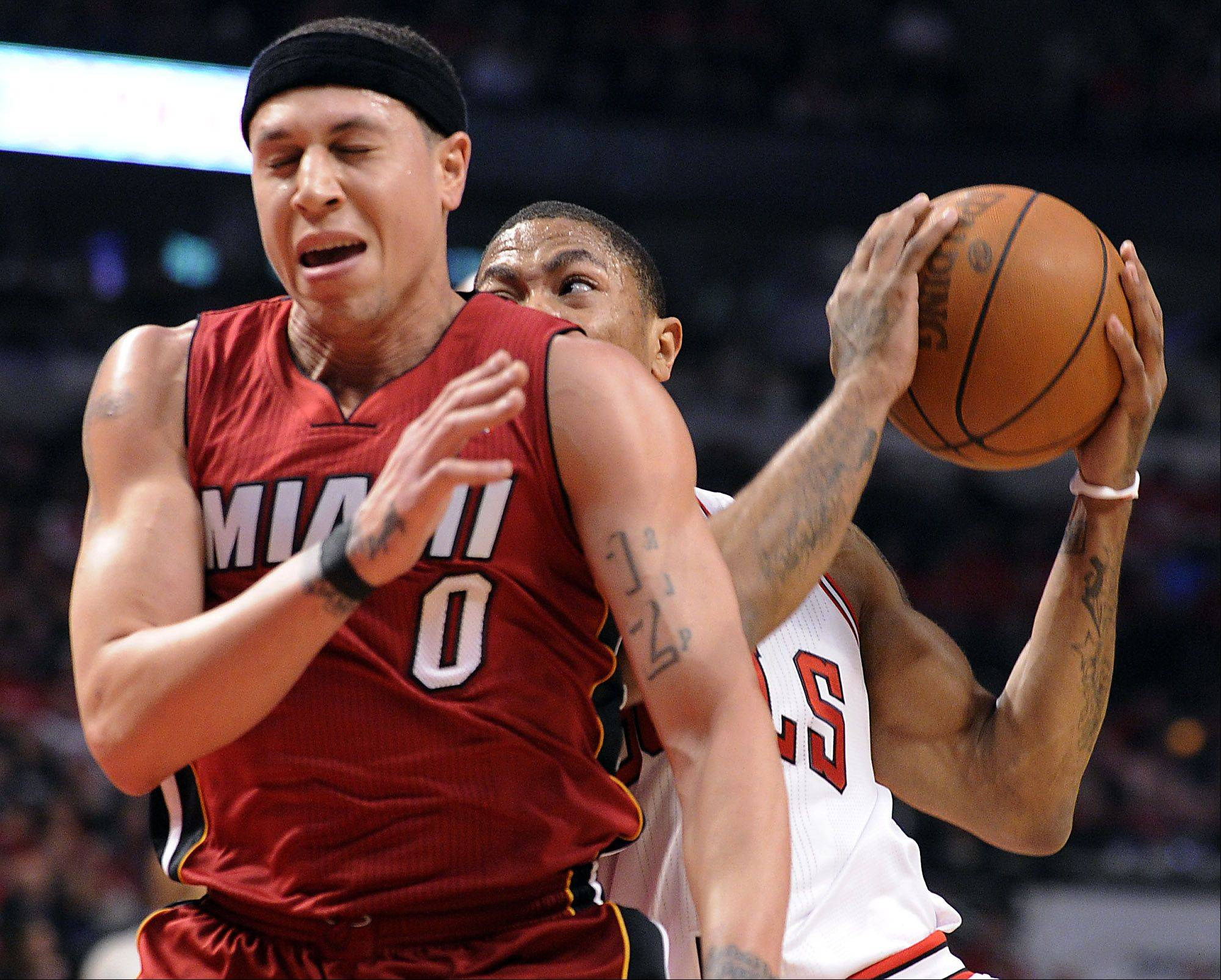 Derrick Rose is blocked on his drive for the basket by the Heat's Mike Bibby in the first half.