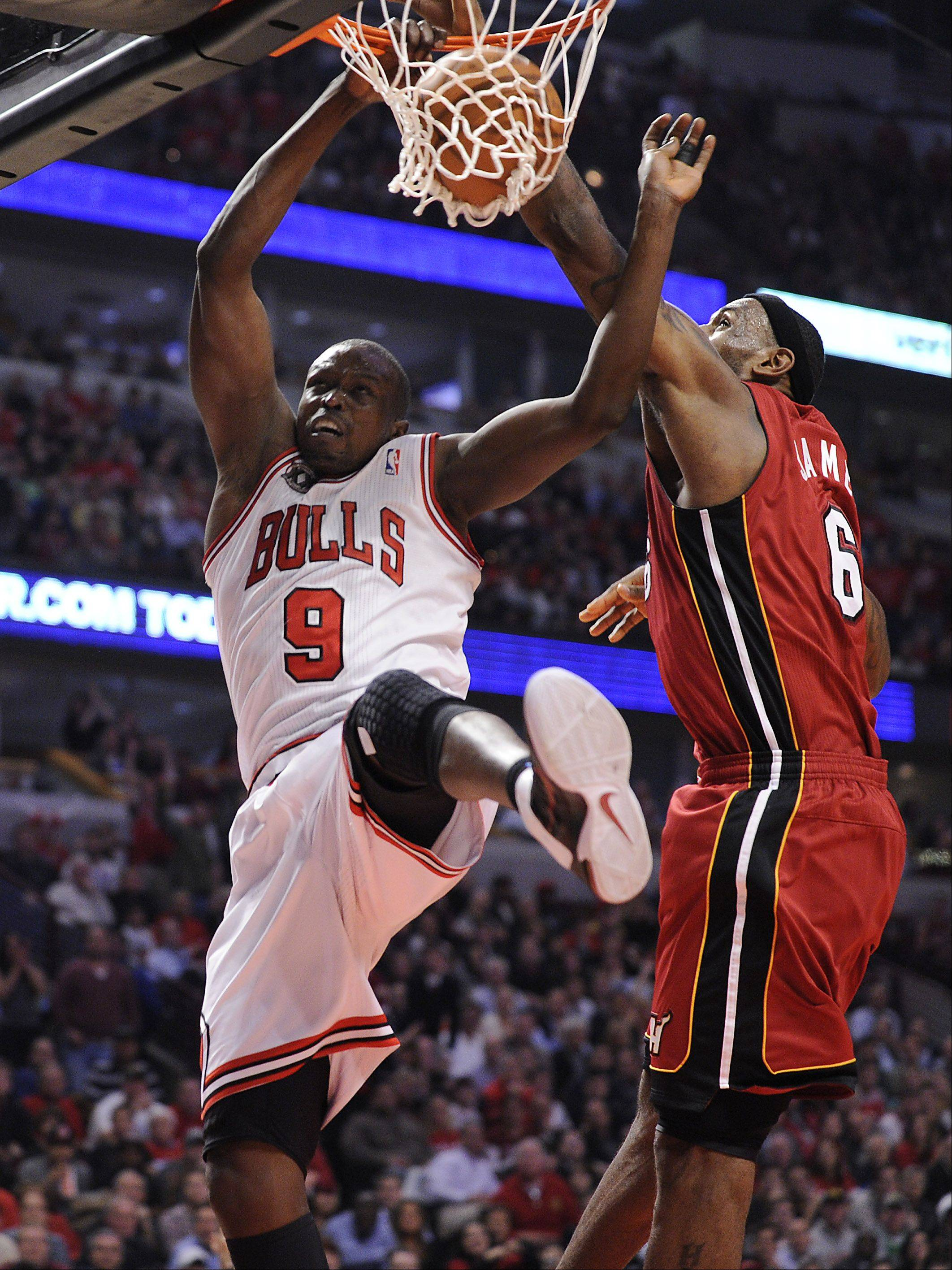 Bulls Luol Deng slams two points home against the Heat's LeBron James in the first half.