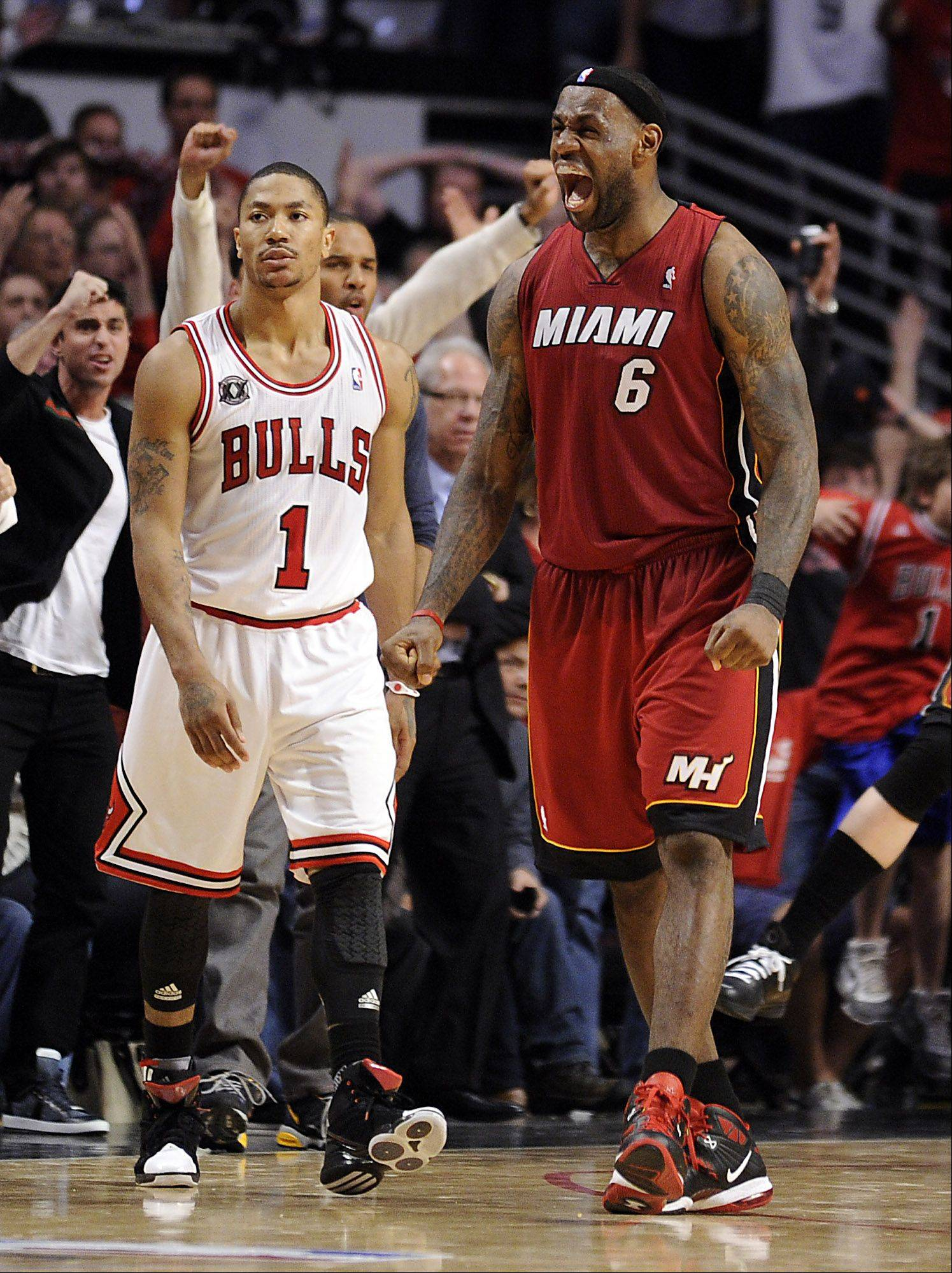 The Heat's LeBron James celebrates his victory as Derrick Rose walks away with a stunned look.
