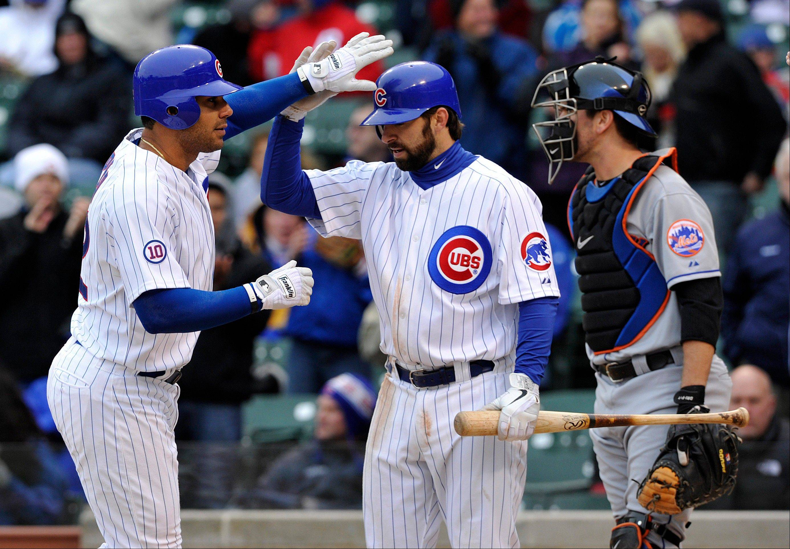 The Cubs' Carlos Pena, left, gets high-fives from Blake DeWitt after Pena hit a 2-run homer in the fourth inning Thursday.