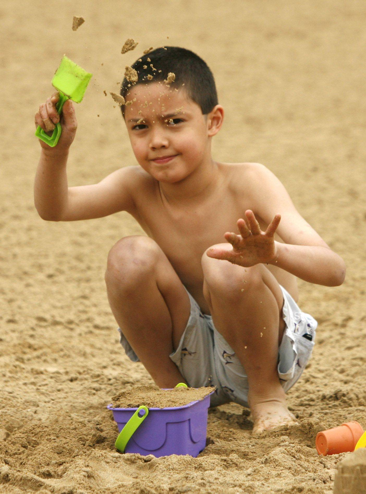 Dakota Lohman, 8, of Naperville, enjoys the sand Saturday during the grand re-opening of Naperville's Centennial Beach.