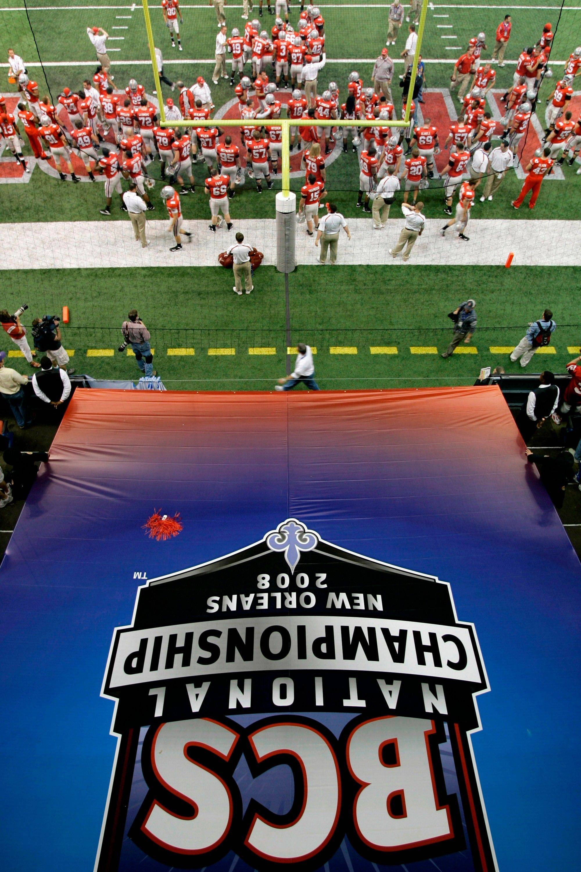 With the BCS logo in the foreground the Ohio State team assembles for a pregame workout before the 2008 national championship game against LSU. NCAA President Mark Emmert and commissioners of the six BCS conferences have said giving college athletes money for personal expenses merits study.