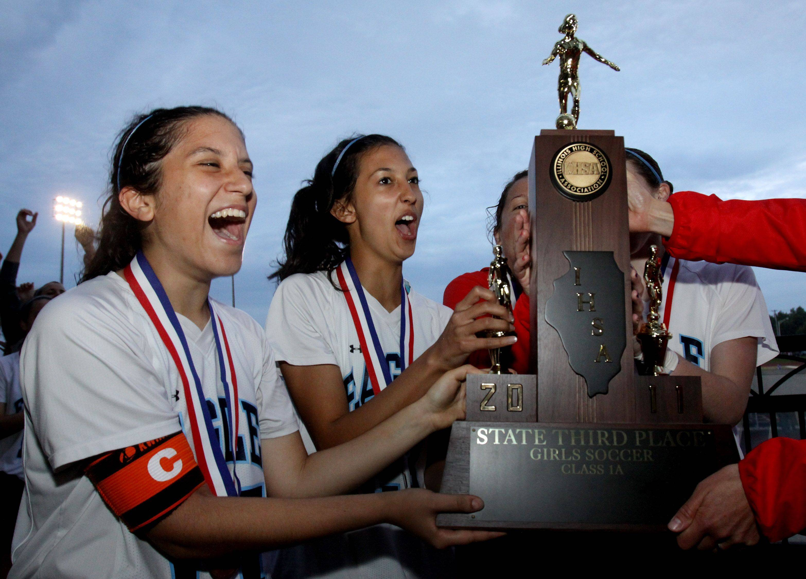 Bridget Paschall, left and Mo Brown, right and the rest of Willows Academy team get their third place trophy for Class 1A state soccer in Naperville on Saturday.