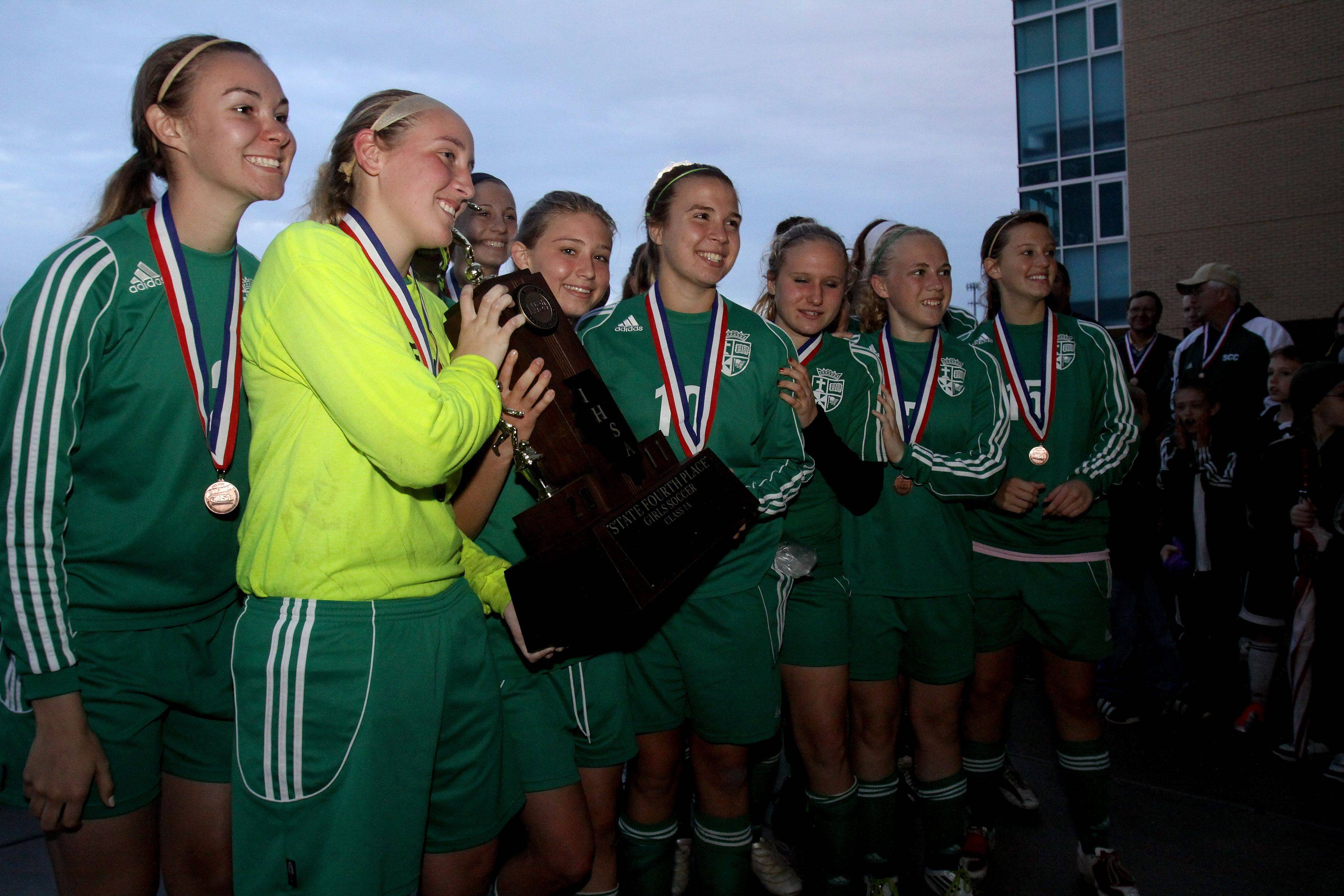 St. Edward pose with their fourth place trophy for Class 1A state soccer in Naperville on Saturday.