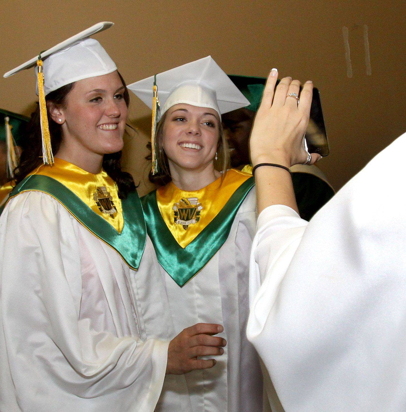 Celena Maskel, left and Maggie Miklasz, right, get a photo taken as they get ready for the Waubonsie Valley High School graduation at College of DuPage in Glen Ellyn on Sunday.