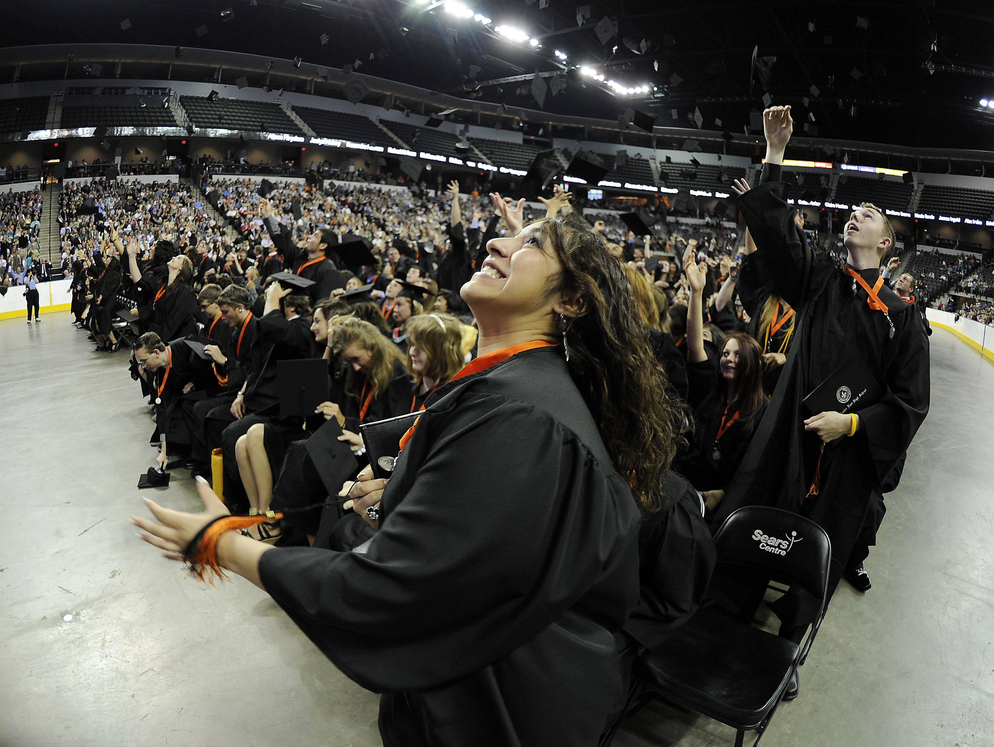 St. Charles East's Priscilla Lachica looks up for her commencement cap among hundreds of others skyward after they became official graduates at the Sears Centre on Sunday.