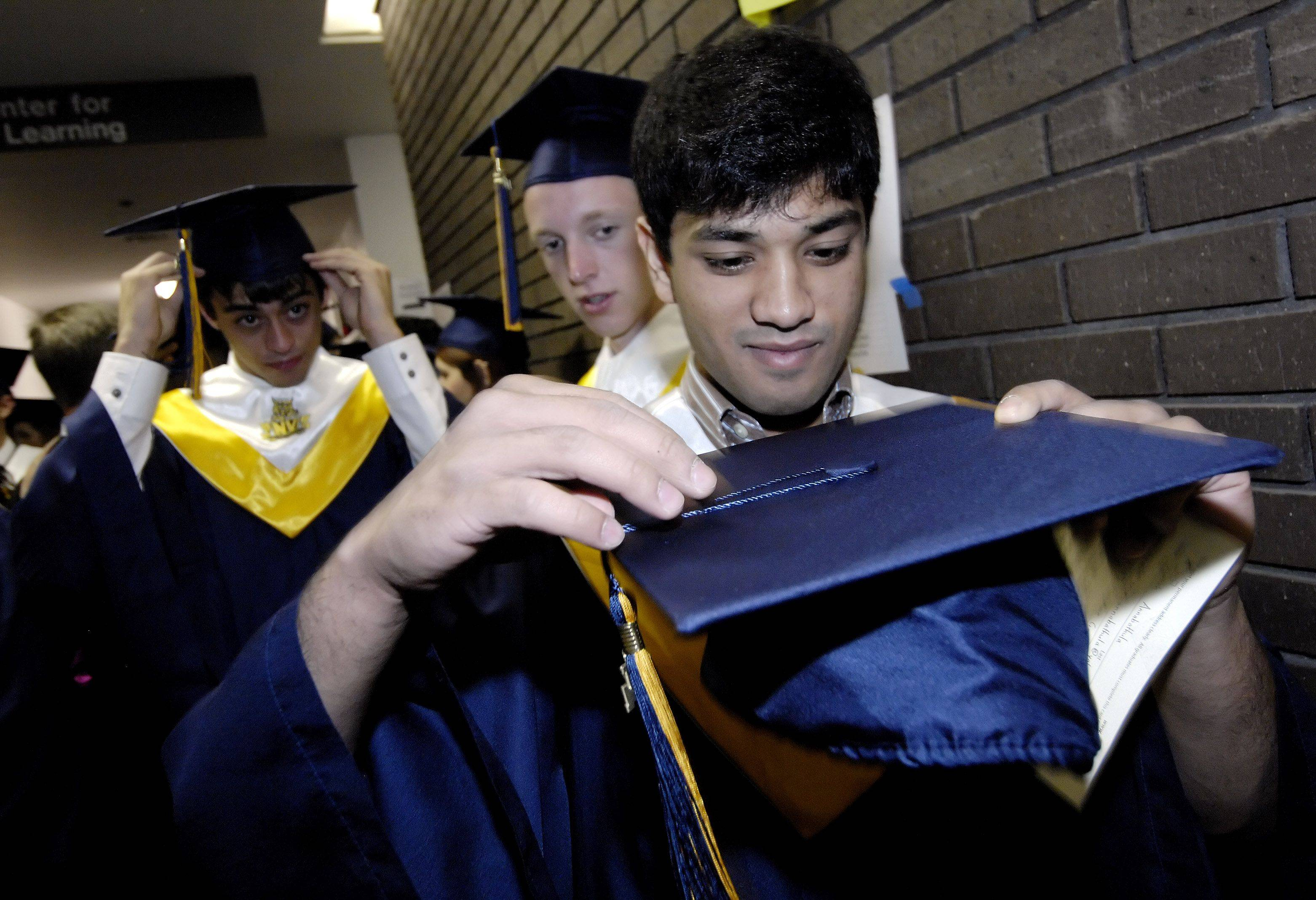 TJ Annabathula affixes his tassel to his mortar board as he waits for the start of the Neuqua Valley High School graduation at the College of DuPage.