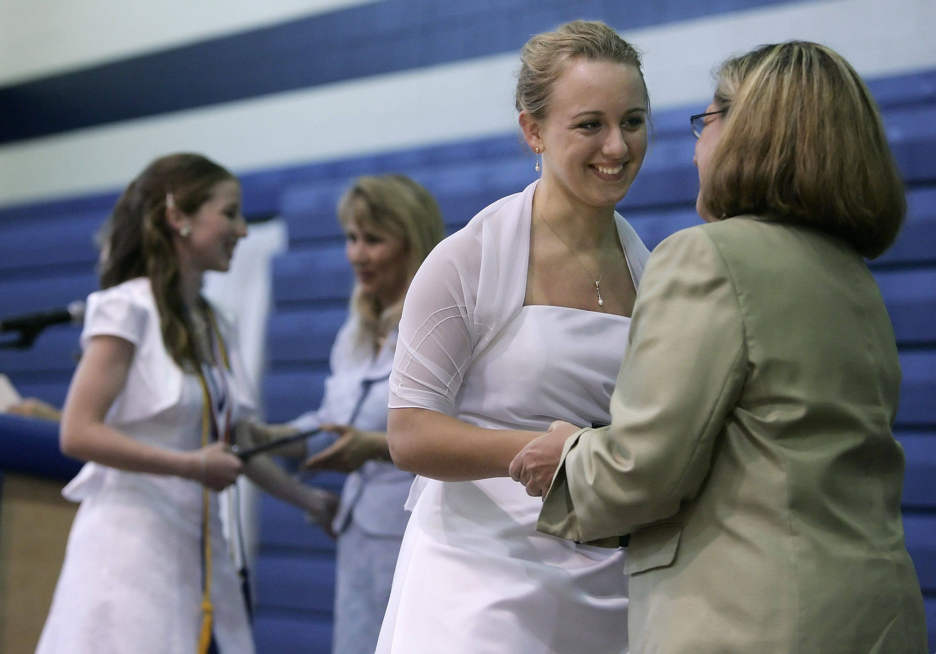 Mary Frelk shakes hands with Mary Keenley, Head of School, after receiving her diploma during The Willows Academy commencement exercises Sunday in Des Plaines. In the back is Mary Gibson as she receives her diploma. The Class of 2011 consisted of 29 graduating seniors.