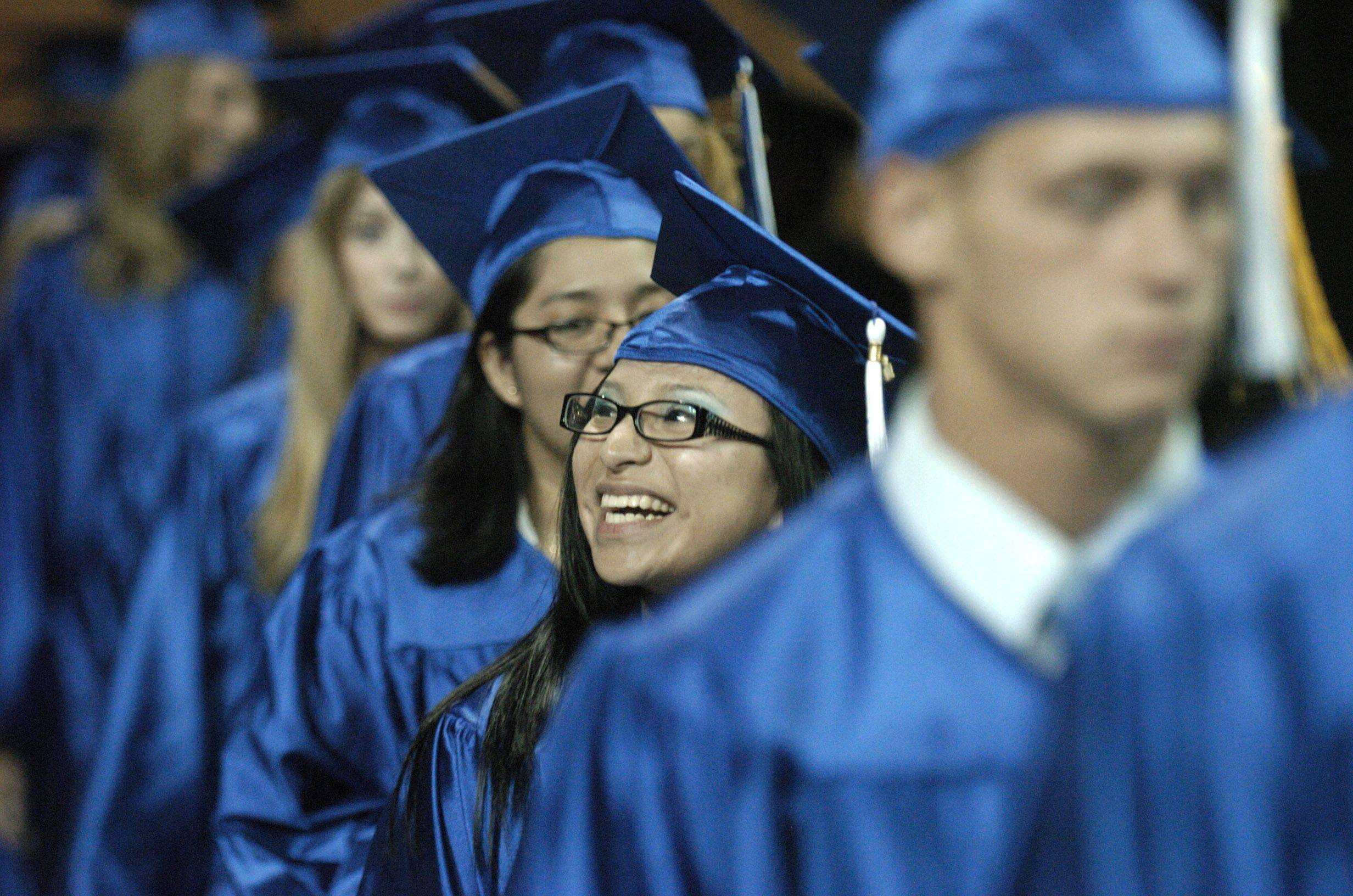 Cynthia Martinez smiles to family as she walks out of the corridor and onto the main floor for Larkin High School's commencement ceremony at the Sears Centre in Hoffman Estates on Saturday.