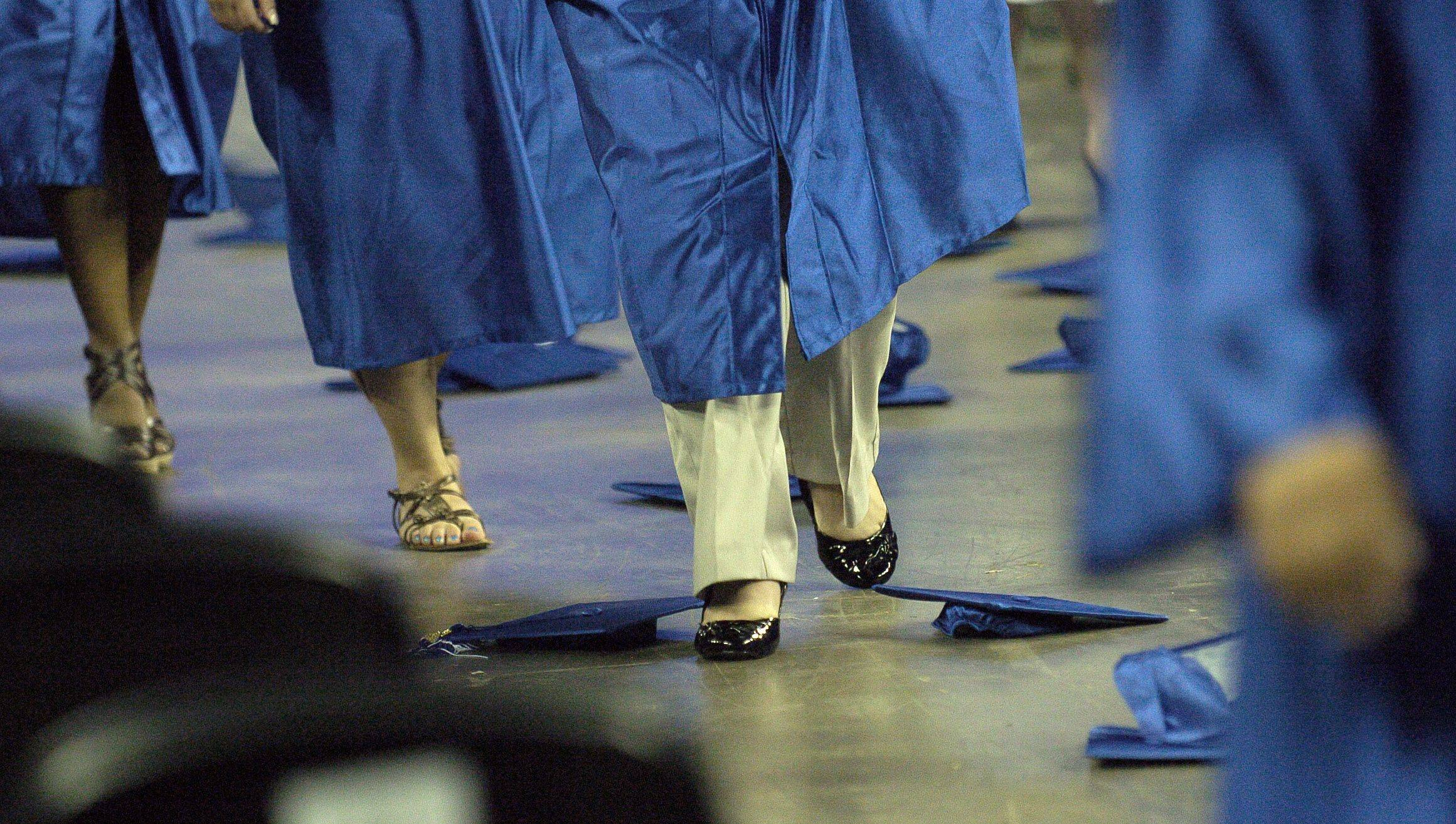 Larkin High School graduates steer their way through discarded caps as they exit the floor after their commencement ceremony at the Sears Centre in Hoffman Estates on Saturday.