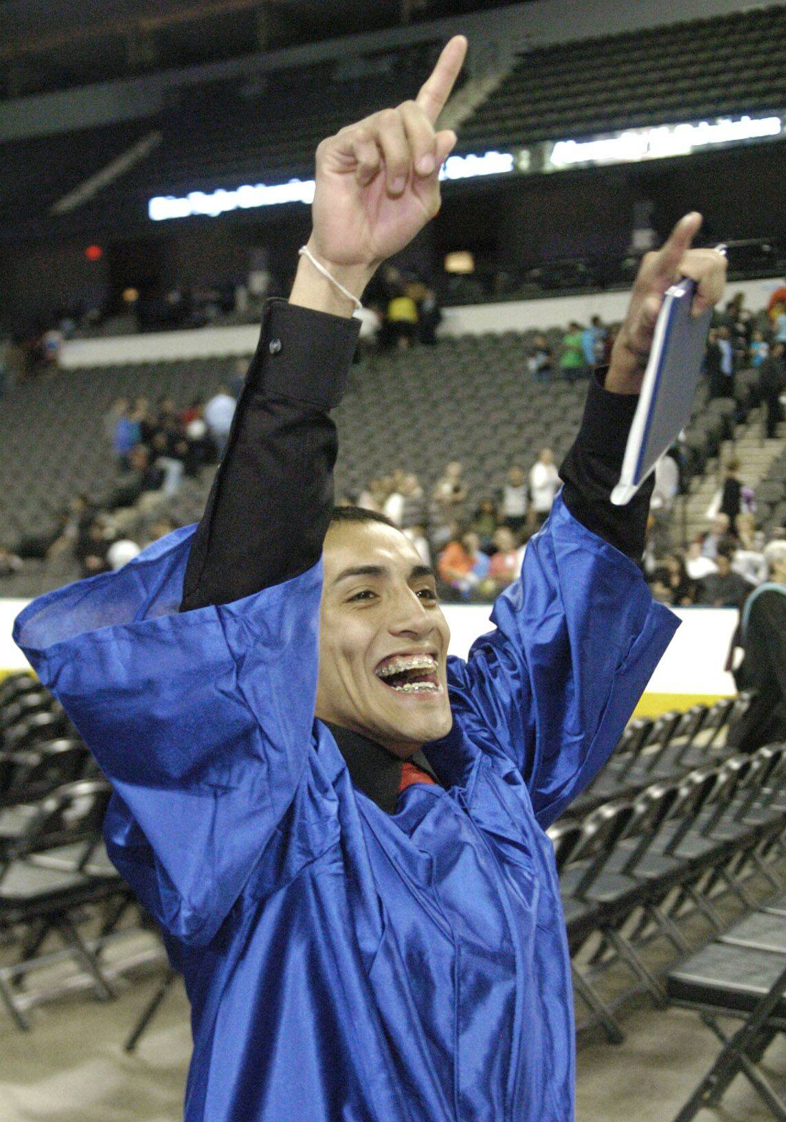 Edgar Zamora cheers to his family as he exits the floor after the conclusion of Larkin High School's commencement ceremony at the Sears Centre in Hoffman Estates on Saturday.