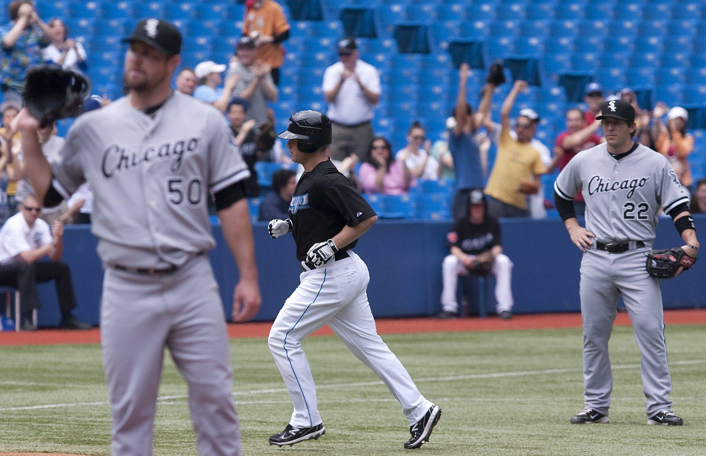 Aaron Hill, center, rounds third base after hitting a grand slam off  White Sox starting pitcher John Danks, left, as third baseman Brent Morel, right,looks on during the first inning Sunday in Toronto.
