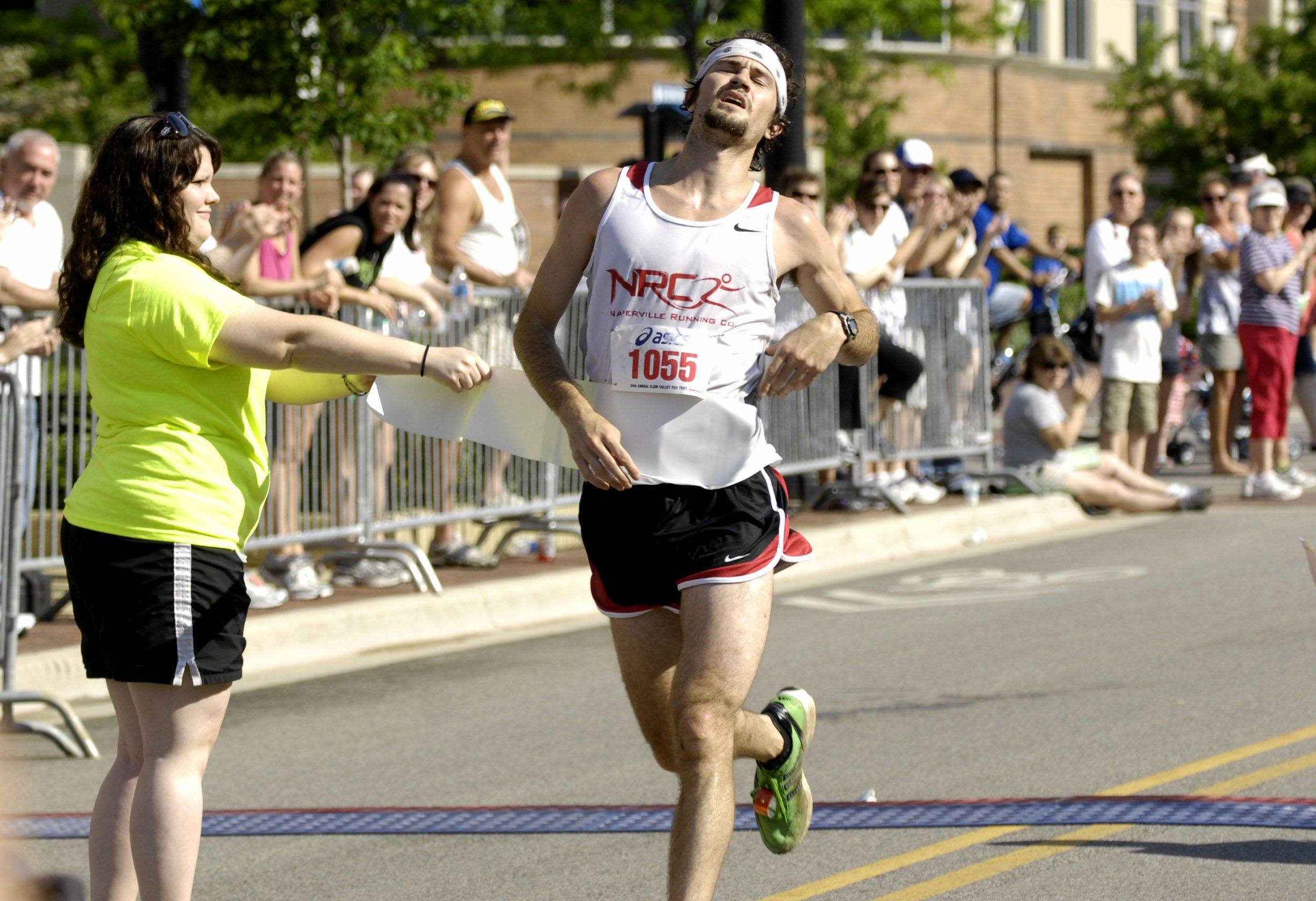 Nik Hird, of the Naperville Running Co., crosses the finish line at the 34th annual Elgin Valley Fox Trot 10-mile race Monday in downtown Elgin.