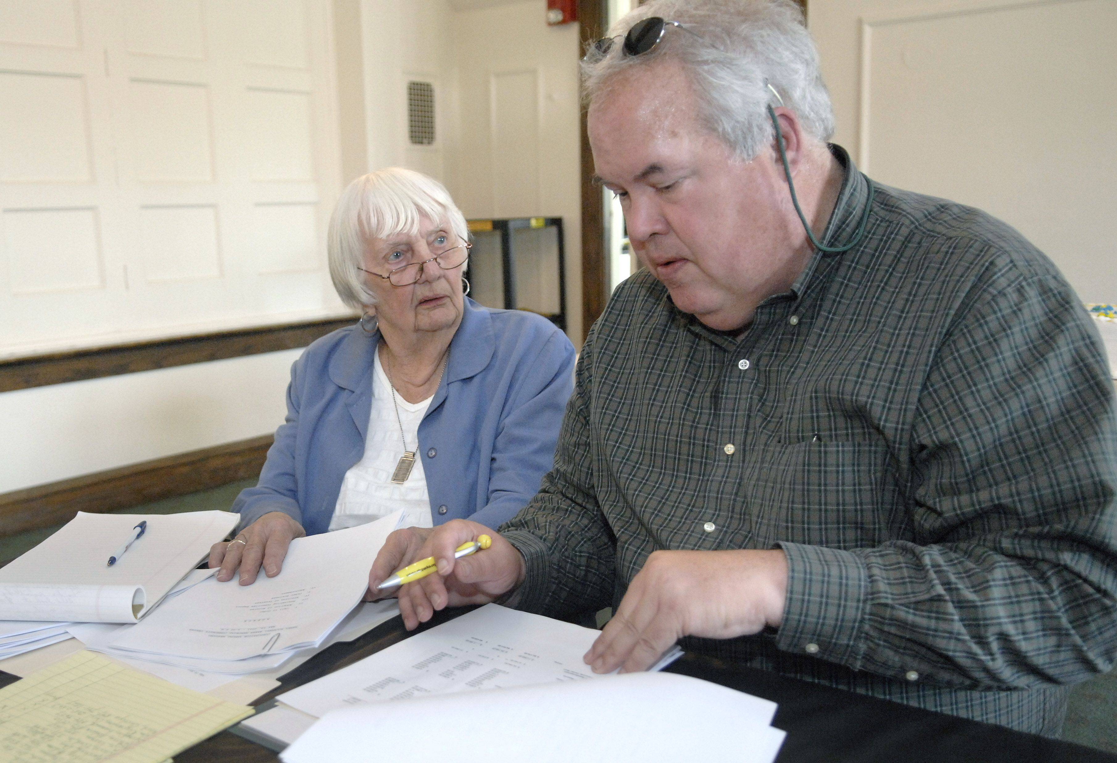 Baker Community Center administrative assistant Carol Glemza and board of directors President John Collins review notes before the annual board meeting May 19.