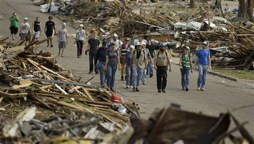 Volunteers walk through a devastated Joplin, Mo. neighborhood Monday, May 30, 2011. An EF-5 tornado tore through much of the city May 22, damaging a hospital and hundreds of homes and businesses and killing at least 139 people.