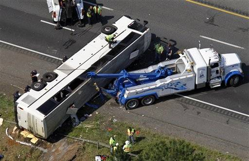 Rescue personnel work on a bus that overturned Tuesday in Bowling Green, Va., killing four people and injuring many more, state police said.