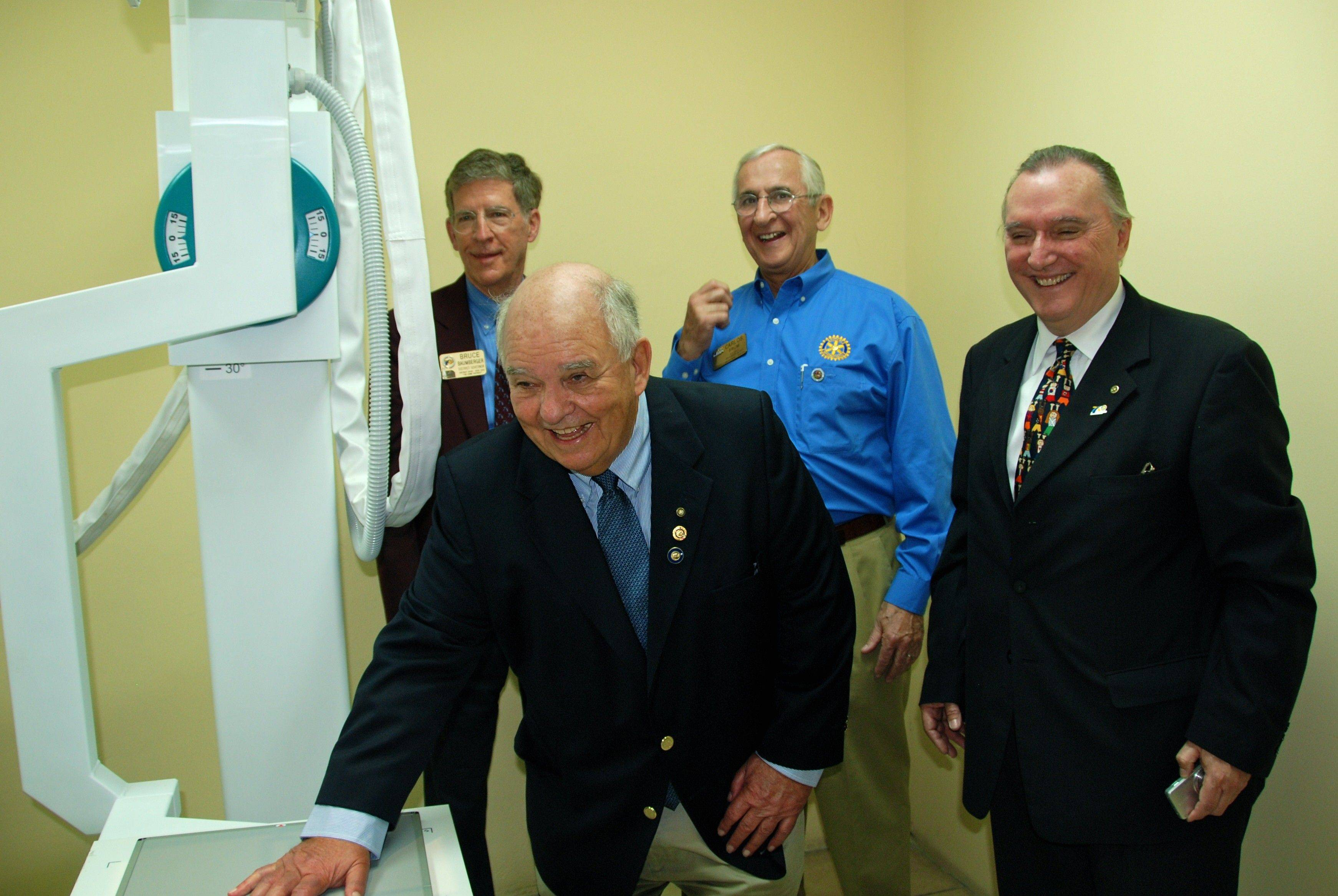In Guatemala City, John Vanden Brink demonstrates how X-ray diagnostic equipment will serve Guatemalans in remote regions. Behind him are Bruce Baumberger and Carlos Frum, Rotary District Governor and District Governor-elect, respectively, of northeastern Illinois-based Rotary International District 6440; and Jorge Aufranc, Past District Governor of Rotary International District 4250.