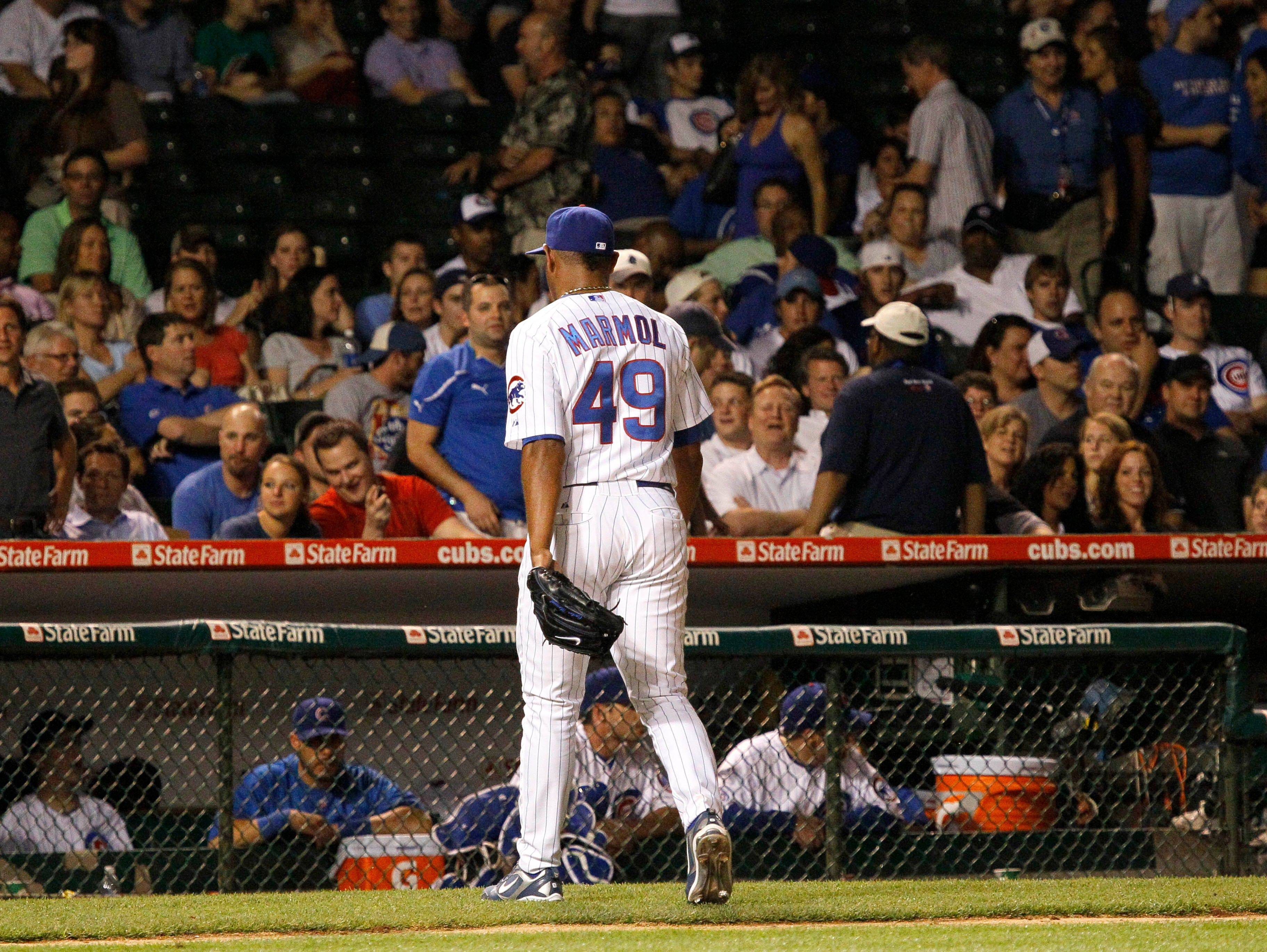 Cubs closer Carlos Marmol walks off the field after giving up 6 runs in the ninth inning Tuesday night.
