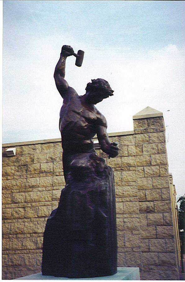 """Self-Made Man,"" installed at State and River streets in Batavia, was created by Bobbie Carlyle. The bronze statue weighs about 750 pounds."