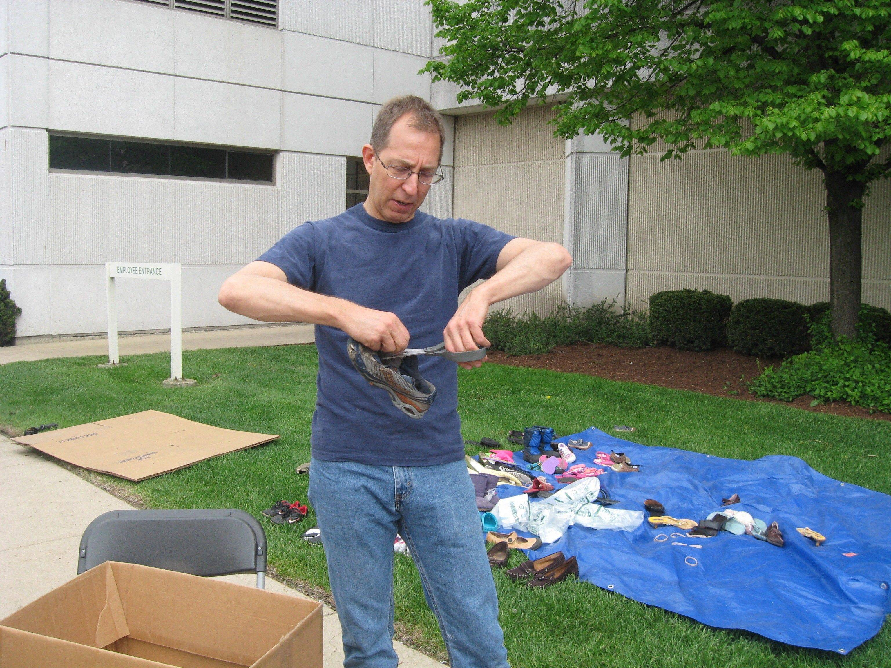 Volunteer Jim Valentine from Our Saviour's Lutheran Church in Arlington Heights cuts metal eyelets out of shoes that will go to Nike's RAS program.