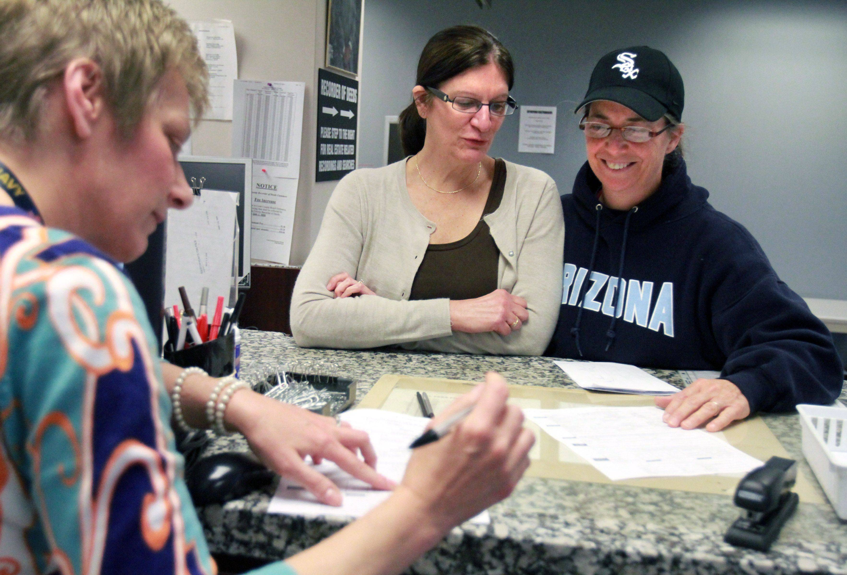 Peggy Ognacevic and Lisa Notarnicola, both of Algonquin, receive help filling out forms for their civil union license from Fran Saloman a clerk in the Bureau of Vital Statistics office at the Cook County Court House in Rolling Meadows on Wednesday, June 1.