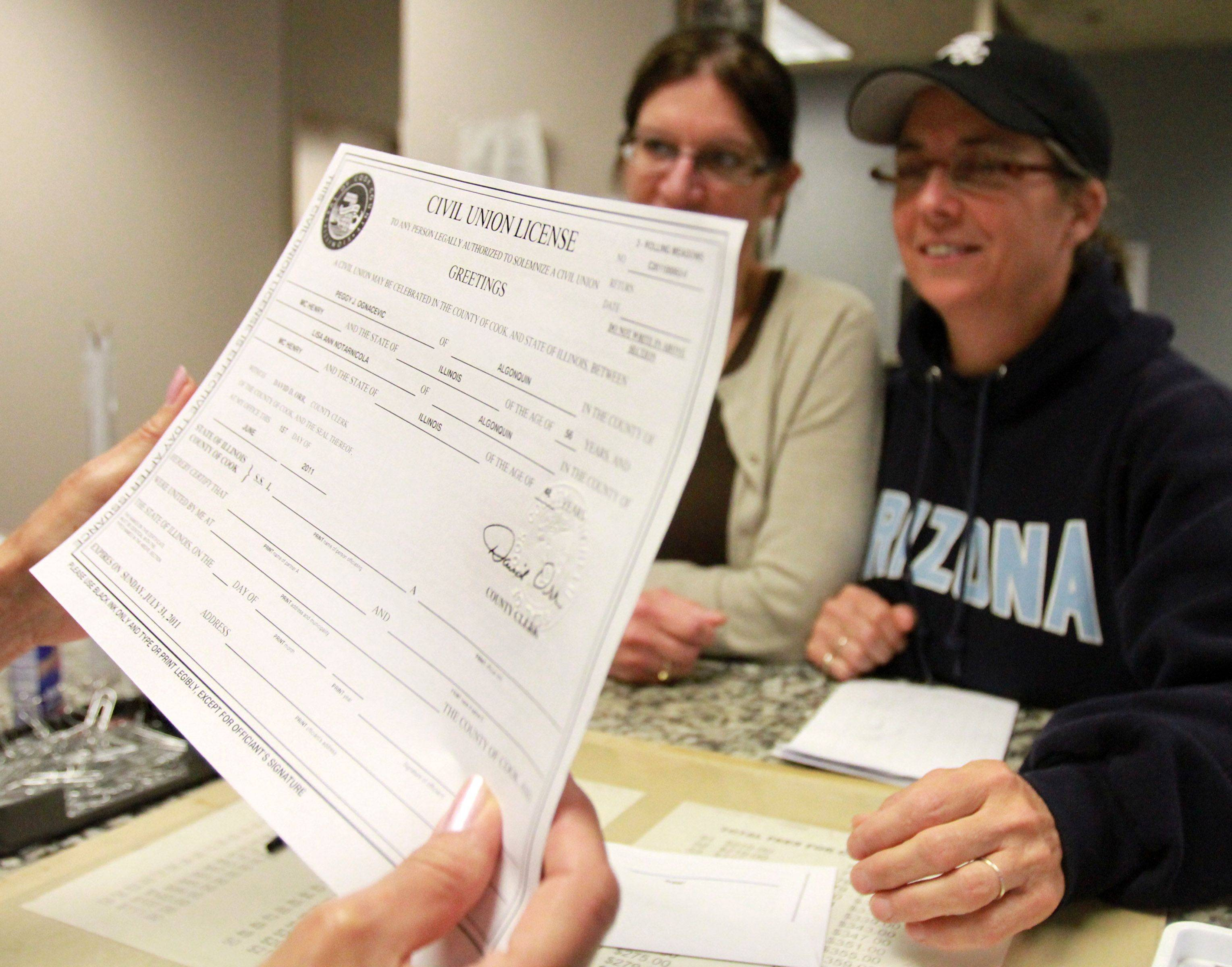Peggy Ognacevic and Lisa Notarnicola, both of Algonquin, receive their civil union license from Lana Yacilla, supervisor in the Bureau of Vital Statistics office at the Cook County Court House in Rolling Meadows on Wednesday, June 1st.