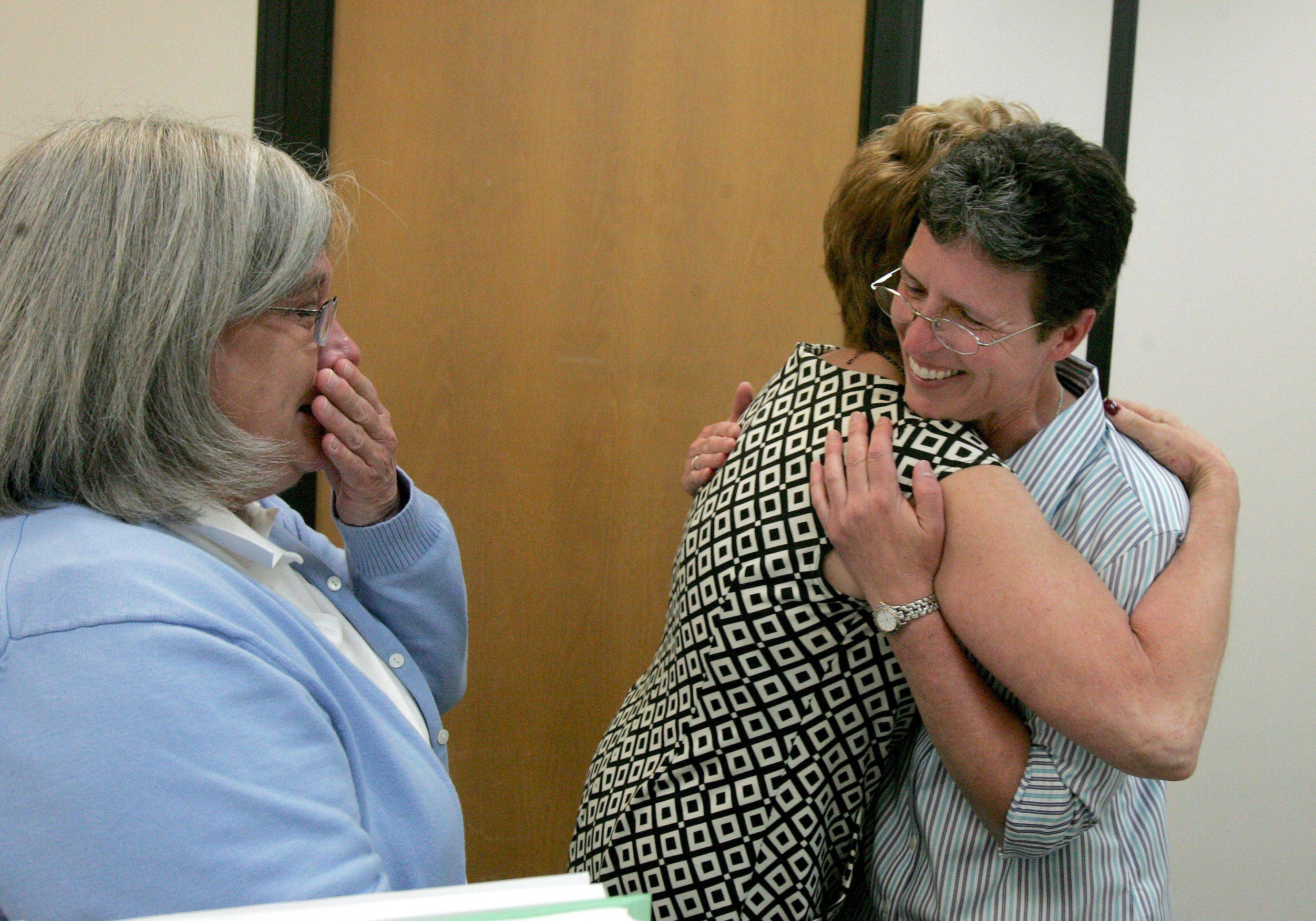 Barb McMillan, left and Roseann Szalkowski, right, of Roselle, get a hug from supervisor Judi Wilkovich at the DuPage County Clerk's office in Wheaton on Wednesday. The couple had just received their civil union license. It was the first day that gay couples could get a civil union license in the state of Illinois.