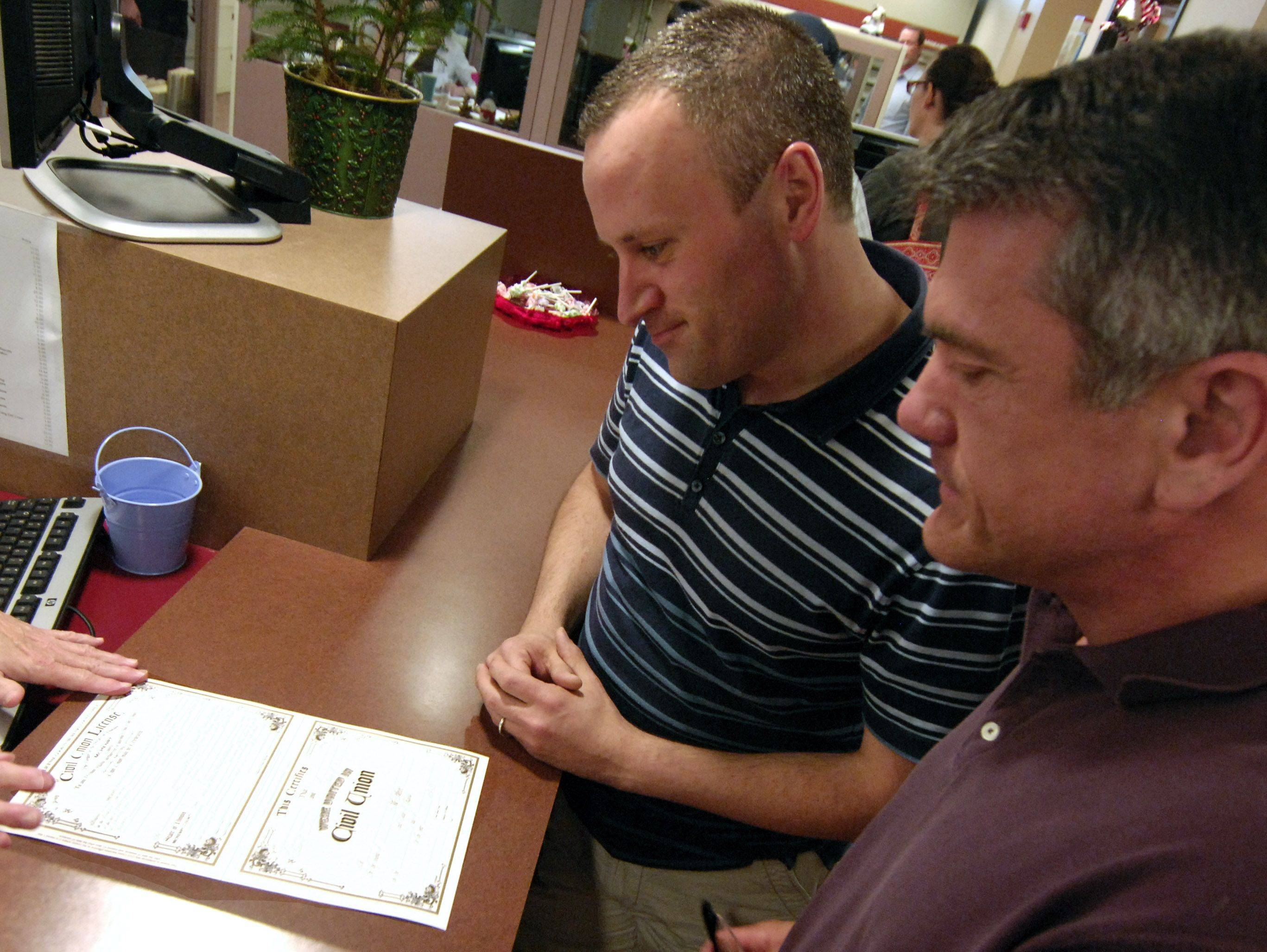 Michael Van Dekreke, left, and Dale Lenig receive their civil union license at the McHenry County clerks office in Woodstock Wednesday.