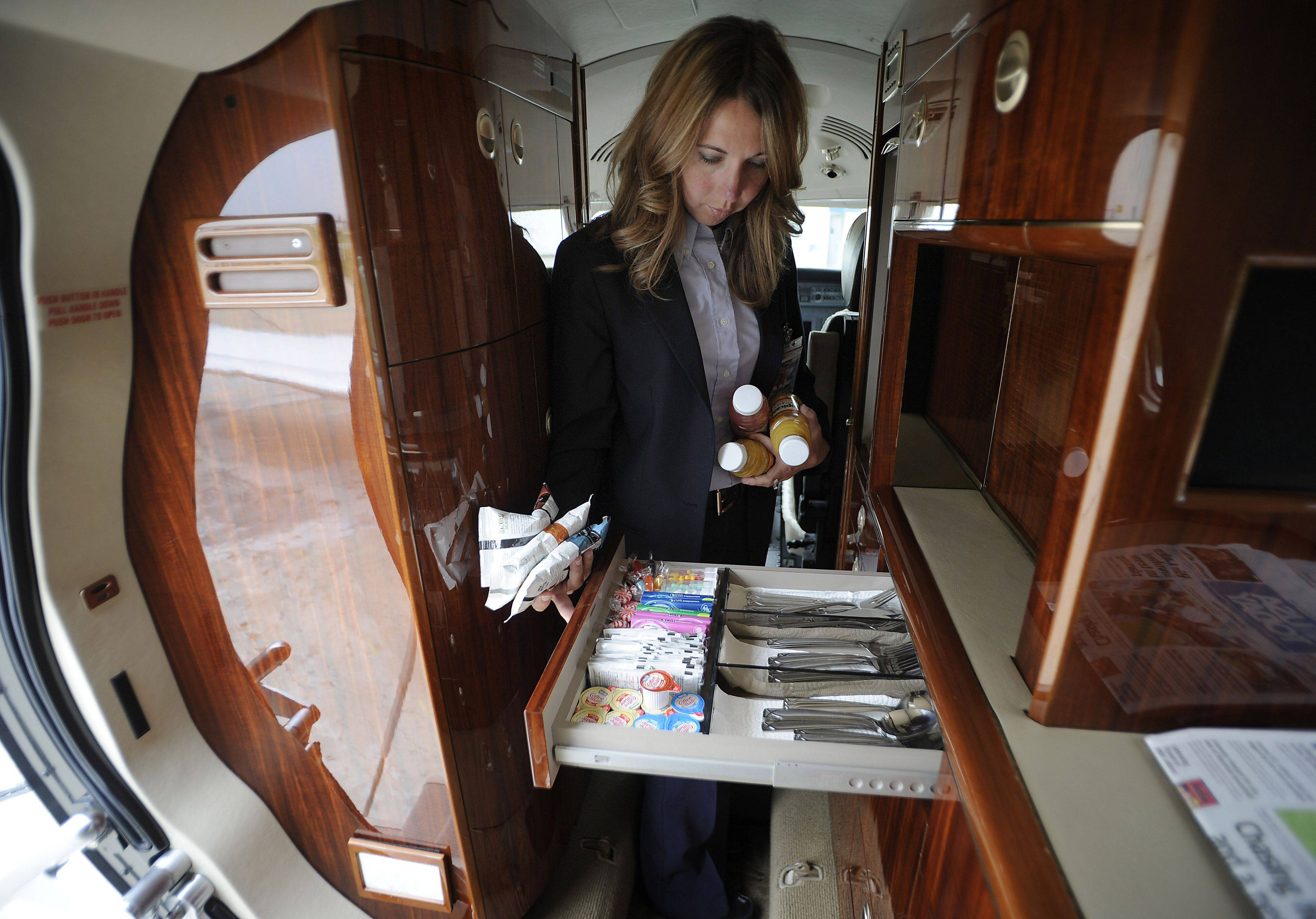 Sorenson checks to make sure all drinks and luxury items for the clients are stocked in her Citation Sovereign aircraft before she flies off to pick up her clients from Chicago Executive Airport.
