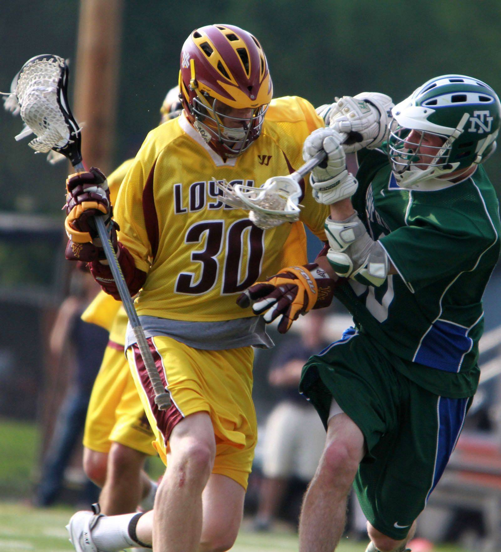 Loyola Academy's Dan O'Malley runs with the ball against New Trier defender Robbie Marren in IHSLA state lacrosse championship game in Oak Park on Saturday.