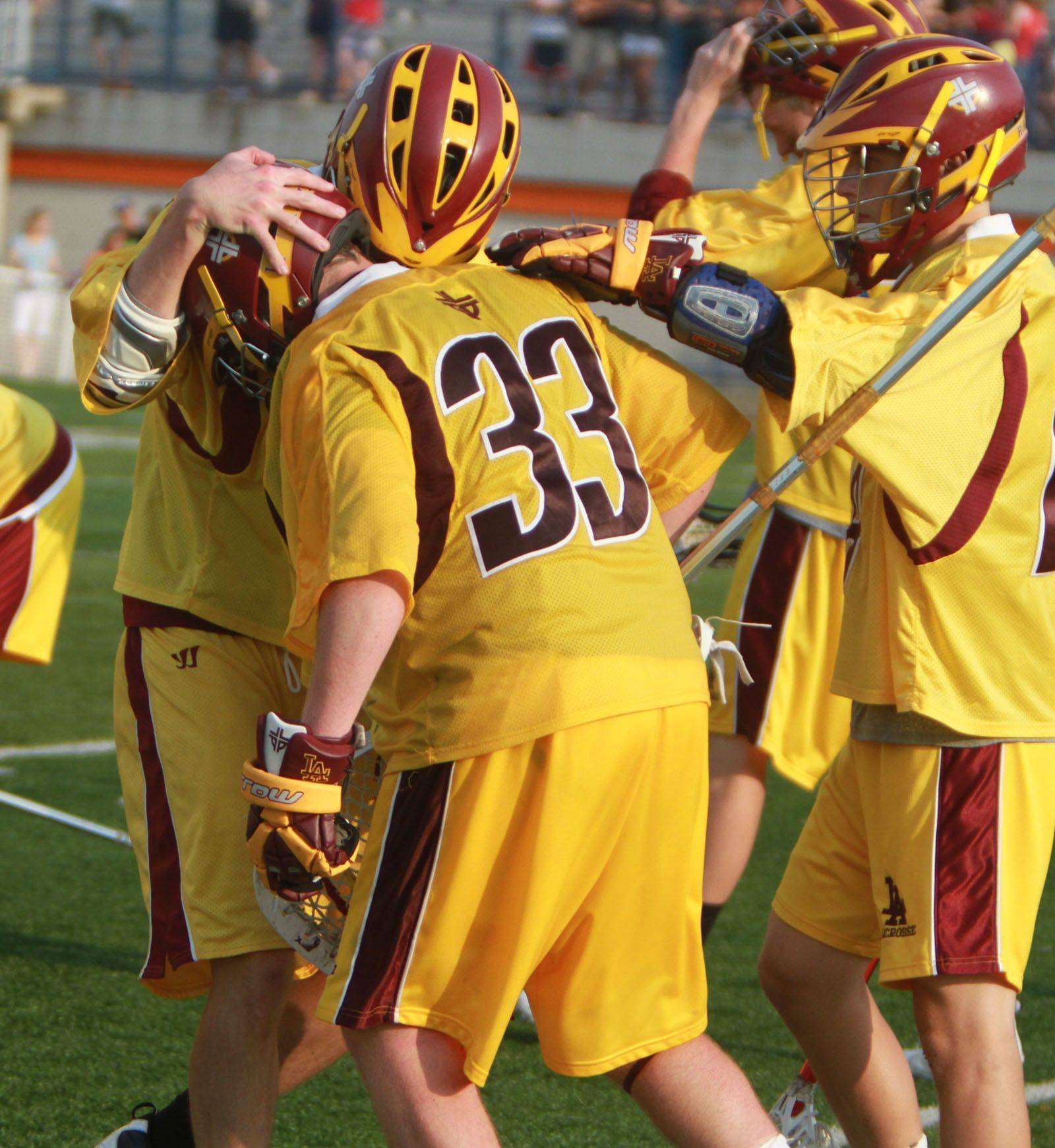 Loyola Academy's Kevin Steger, center, gets a hand from teammates after losing the IHSLA state lacrosse championship to New Trier in Oak Park on Saturday.