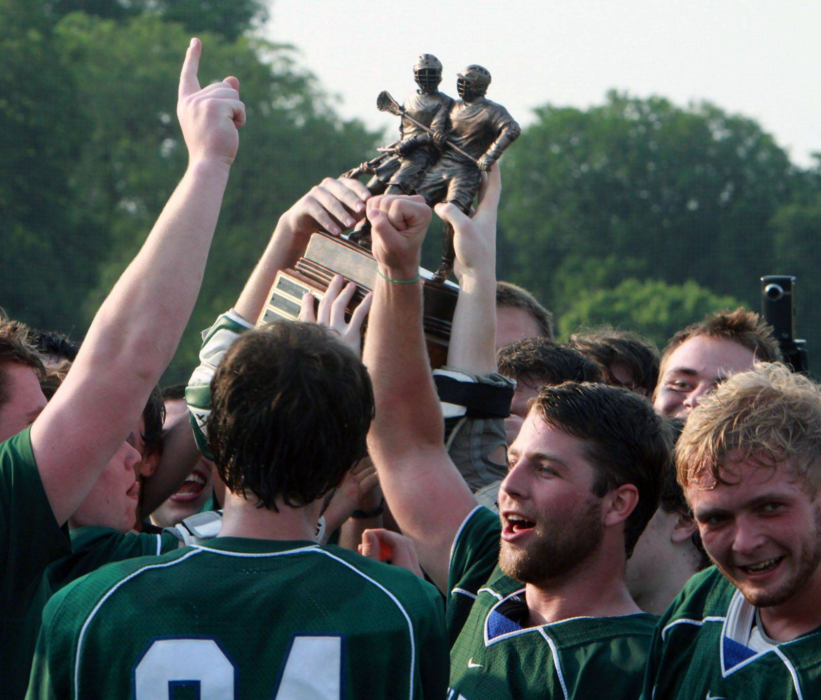 New Trier celebrates with the in IHSLA state lacrosse championship trophy after winning over Loyola Academy in Oak Park on Saturday.