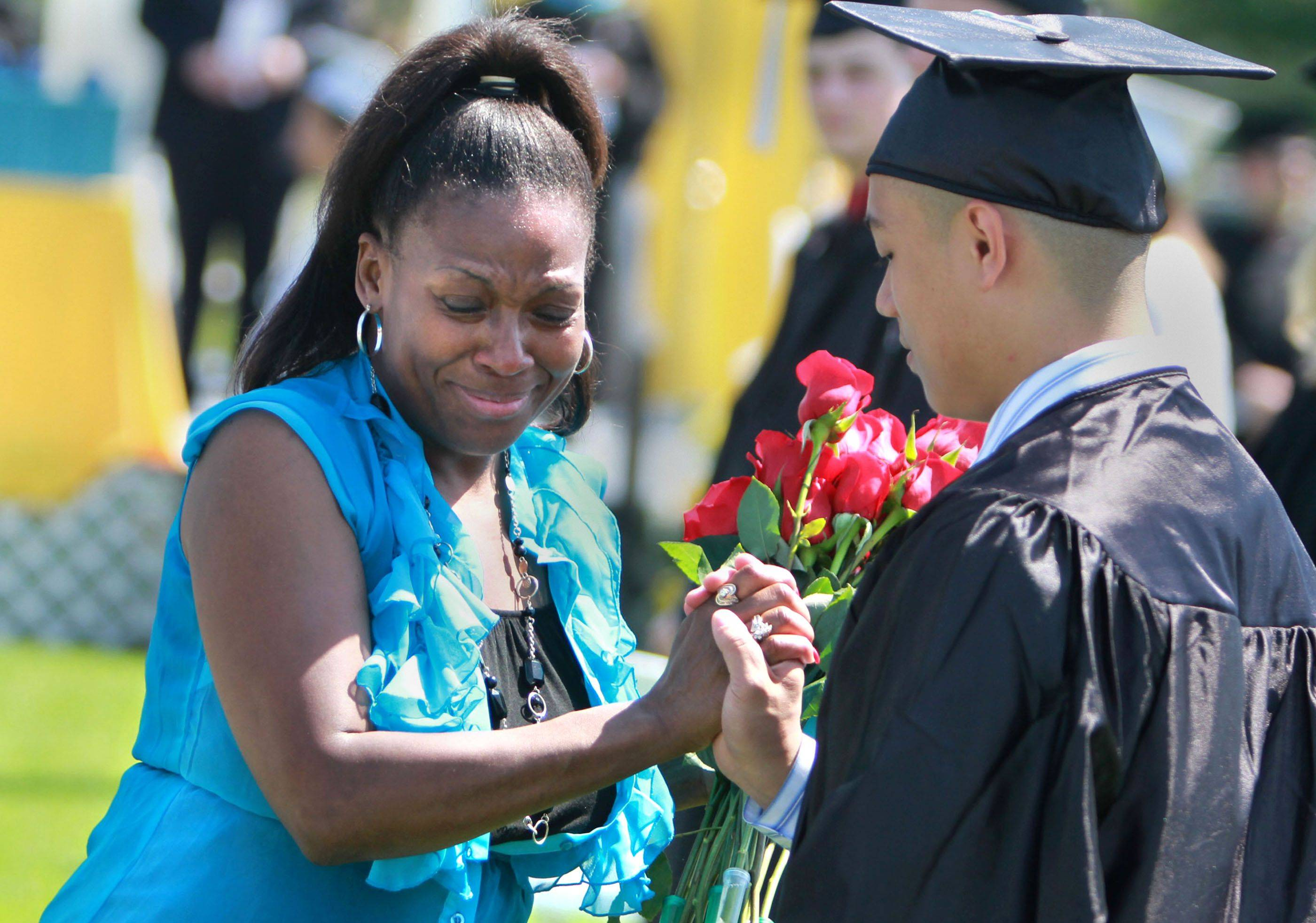 Loreene Taylor received her son Choice's diploma, roses from 20 students and a hand from Jacob Manlucu during Maine West High School's graduation ceremony Sunday in Des Plaines. Choice Taylor, 17, was struck and killed by a truck November 5th, 2010 in Des Plaines, while walking home from work.