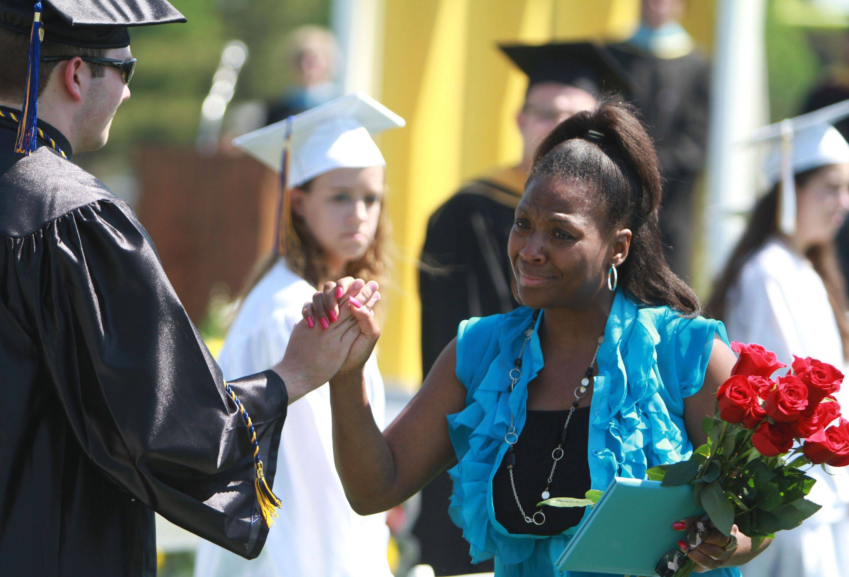 Loreene Taylor gets handshakes, hugs and roses from fellow Maine West High School graduates Sunday as she accepts the diploma for her son, Choice. The 17-year-old was struck and killed by a truck while walking home from work in November.