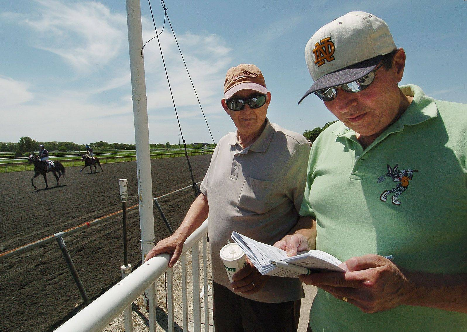 Veterans of many sporting events and casinos, Milwaukee retirees Ronald Schleicher, left, and Jim Herro say Arlington Park is more about the horses and atmosphere than the gambling.