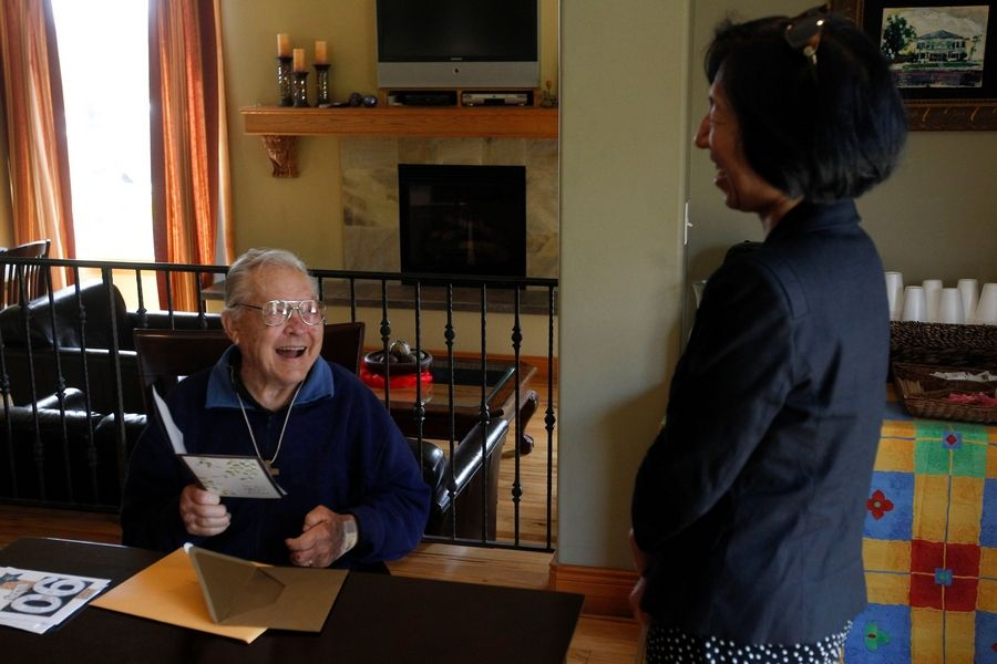 Bob Krause, left, opens a birthday card from his doctor, Patricia Wu, during his 90th birthday celebration.
