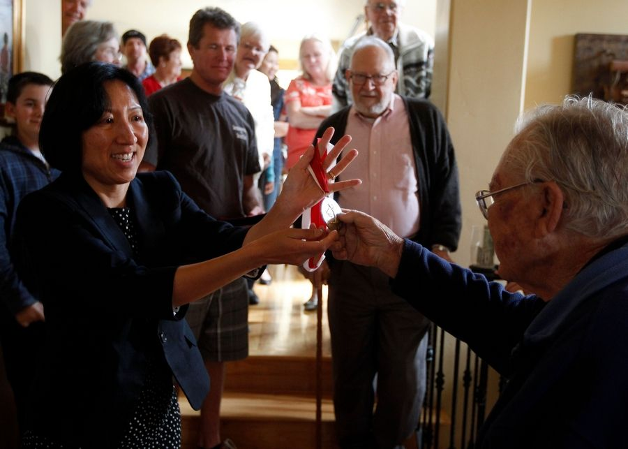 Bob Krause, right, gets a medal from his doctor Patricia Wu and the Boston-based Joslin Diabetes Center during his 90th birthday celebration in San Diego,
