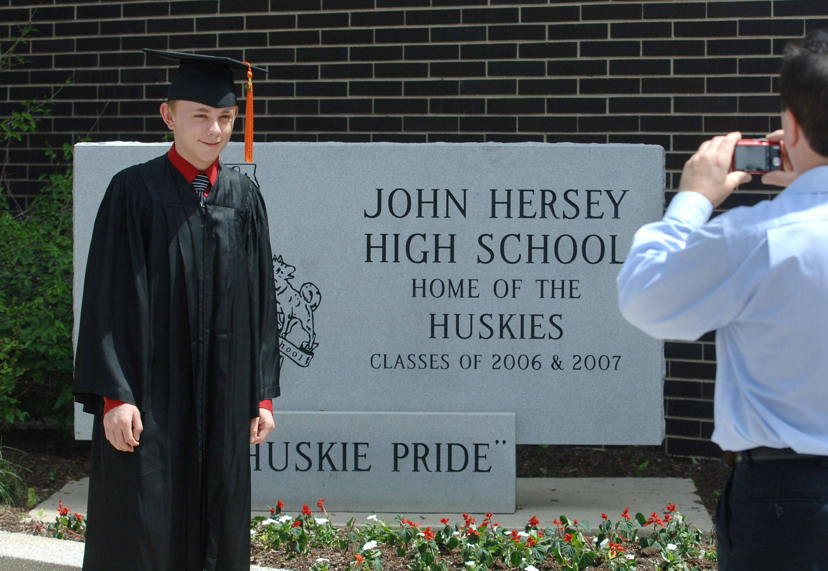 Hersey High School student Eric Adams has his photo taken by his dad, Ken Adams, during Sunday's graduation ceremony at the Arlington Heights school.