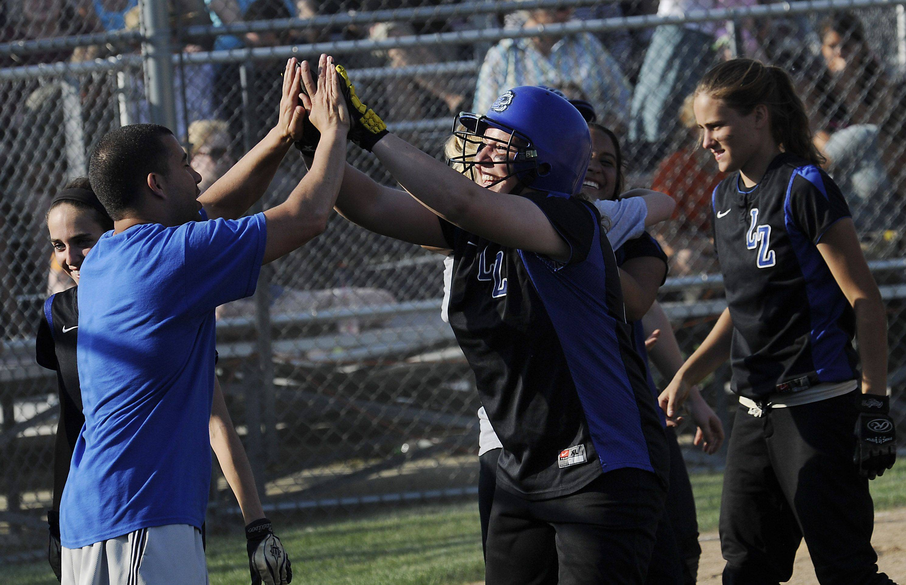 Lake Zurich's pitcher Megan Mattera hits a solo homer in the sixth inning that brought many Bears fans smiles and a 2-0 lead over New Trier in the Class 4A Glenbrook South softball supersectional title game on Monday.