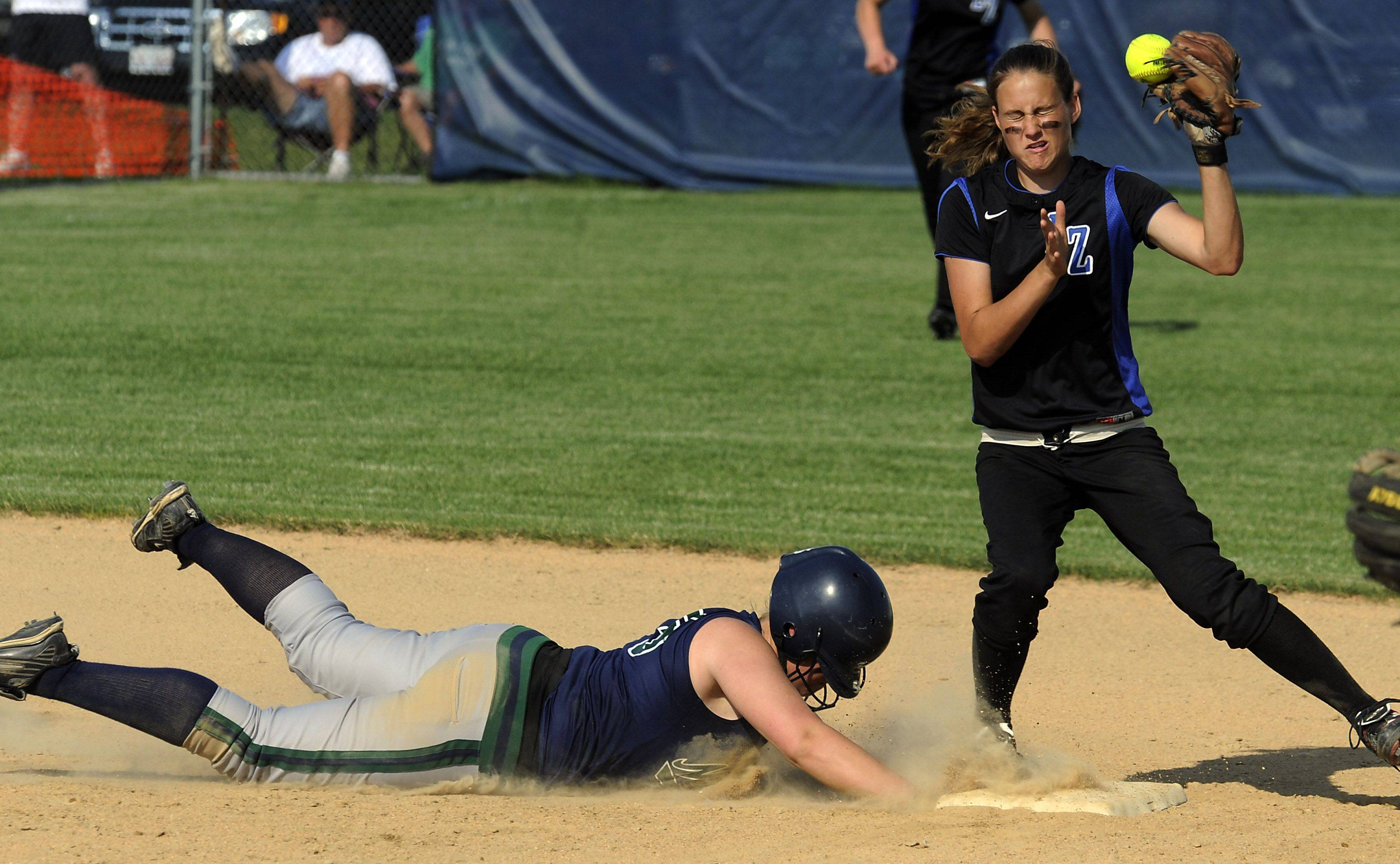 Lake Zurich shortstop Tabbetha Bohac mishandles the ball in this pick-off attempt on New Trier's Chelsea Delaney in the 4th inning in the Class 4A Glenbrook South softball supersectional title game on Monday.
