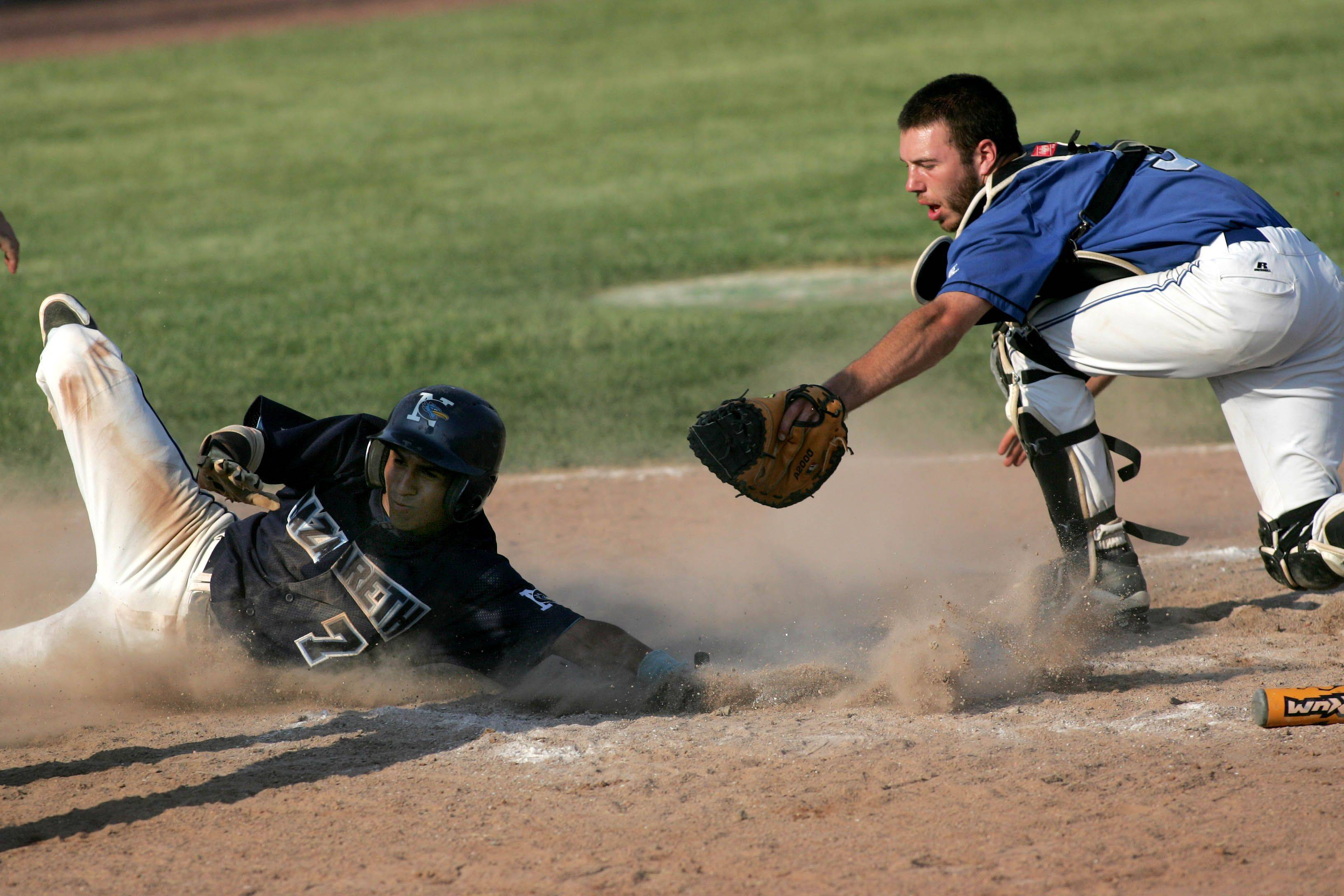 St. Francis catcher K.C. Zimmerman reaches out to tag Michael Barajas of Nazareth Academy, but he was safe at home in Class 3A supersectional baseball Monday in Naperville.