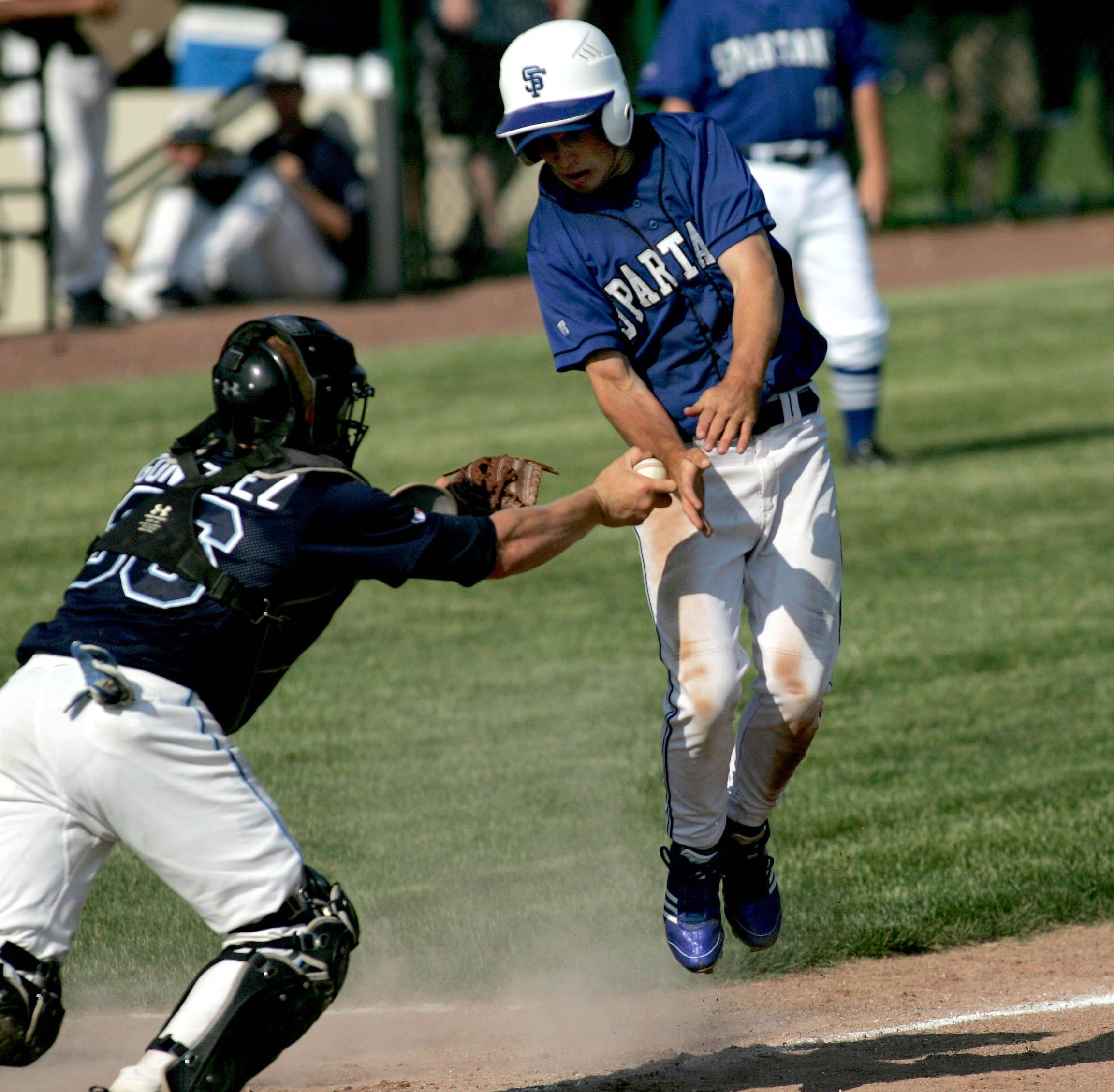 Scott Purdom of St. Francis, right, gets tagged out by Nazareth Academy catcher Justin Gonzalez at home after he tried to steal first in Class 3A supersectional baseball action Monday in Naperville.